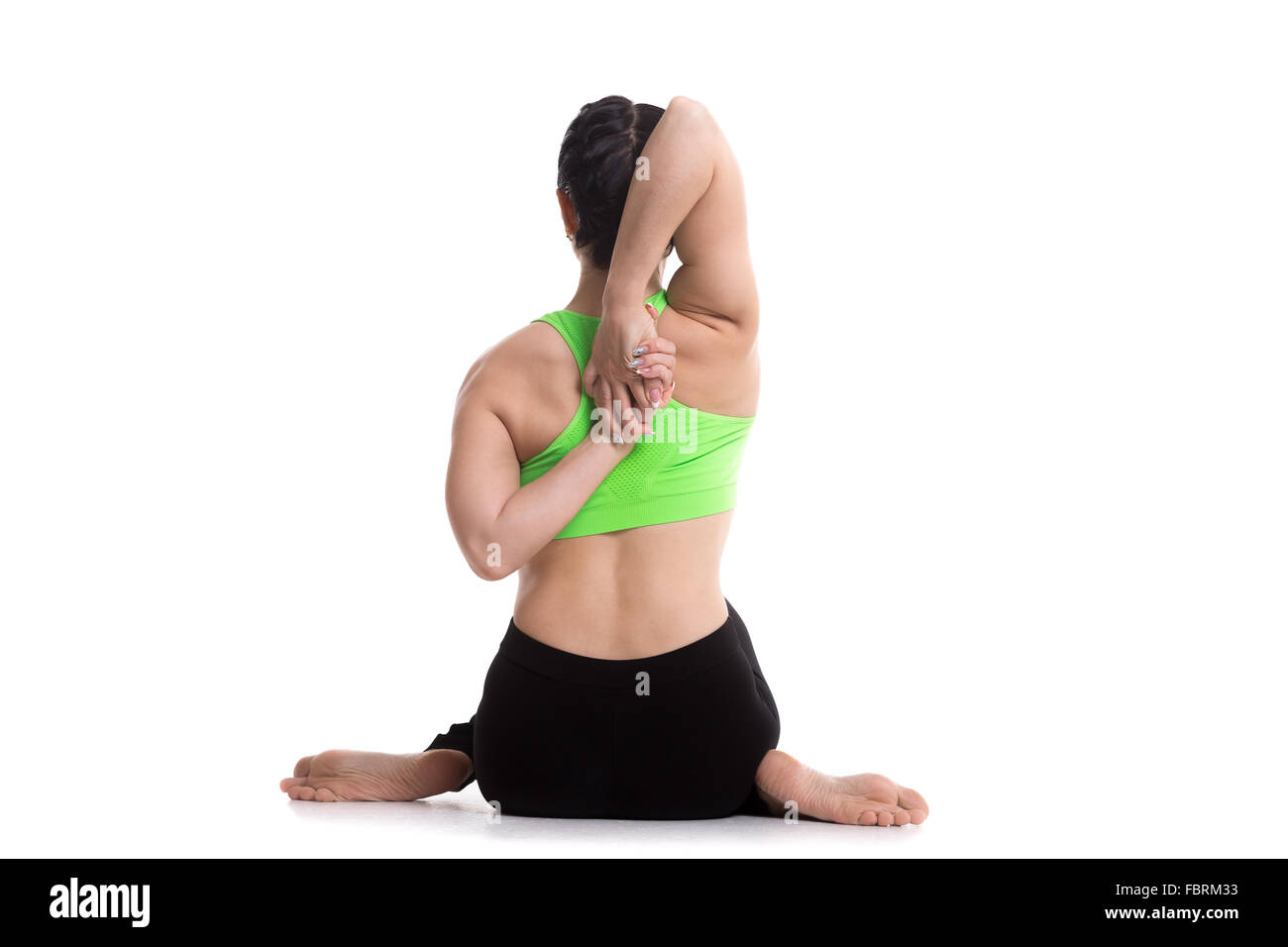 Sporty girl doing yoga training, sitting in Gomukhasana, Cow face pose, asana for stretching triceps, shoulders - Stock Image