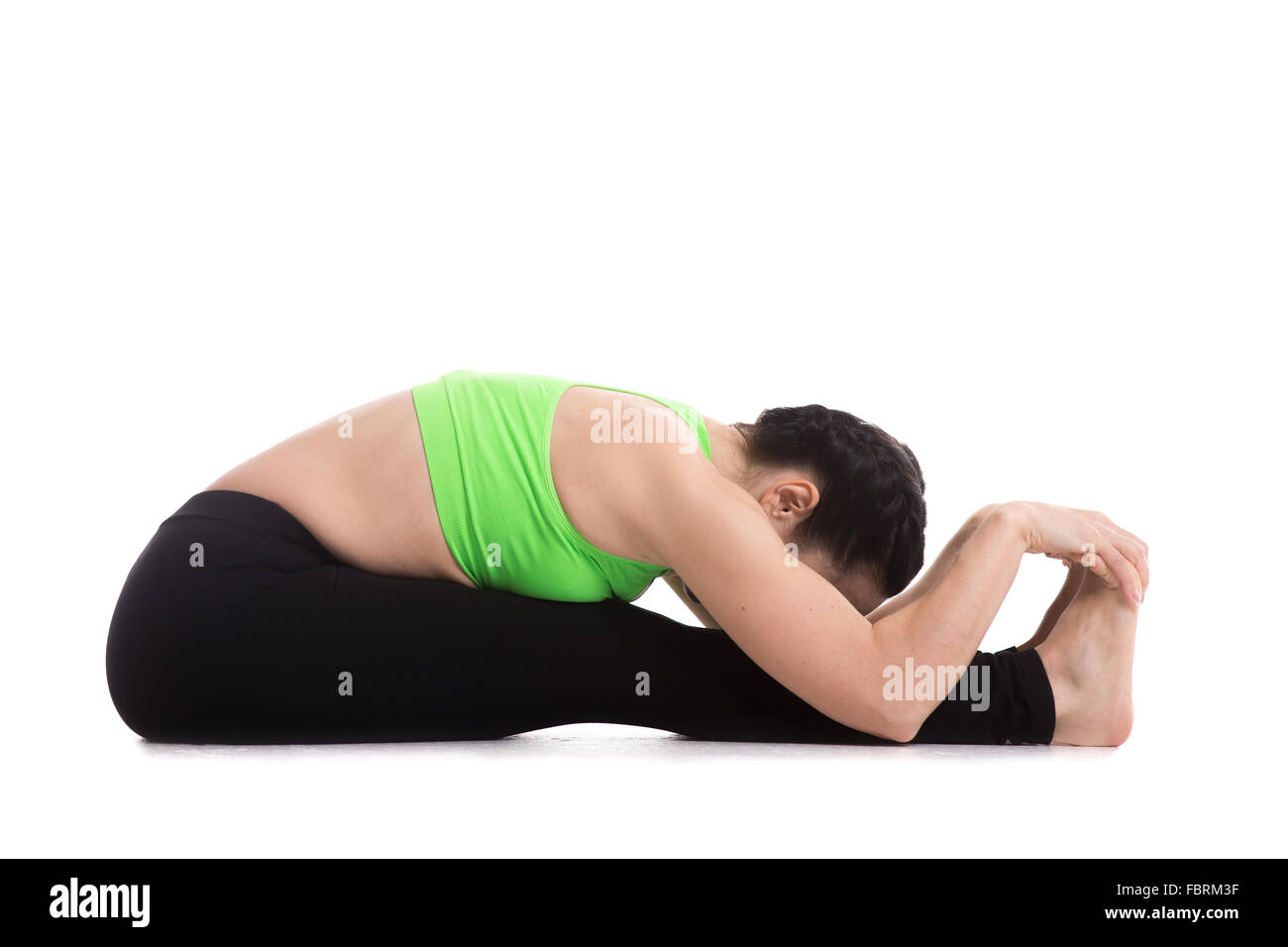 Sporty beautiful girl does yoga workout, lean on her knees in seated Forward Bend pose (Intense Dorsal Stretch), - Stock Image