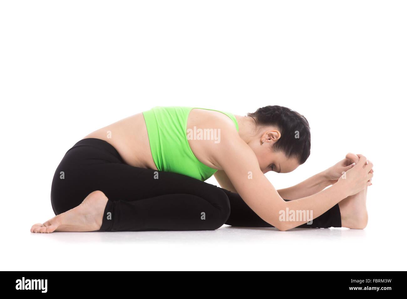 Beautiful serene girl sitting in Triang Mukha Eka Pada Paschimottanasana yoga asana, Three-Limbed Forward Bend pose - Stock Image