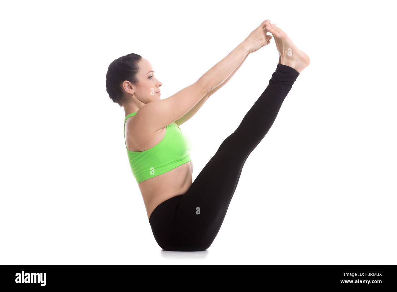 Beautiful serene girl sitting in Ubhaya Padangusthasana asana, Both Big Toe pose, balancing yoga posture, stretching - Stock Image