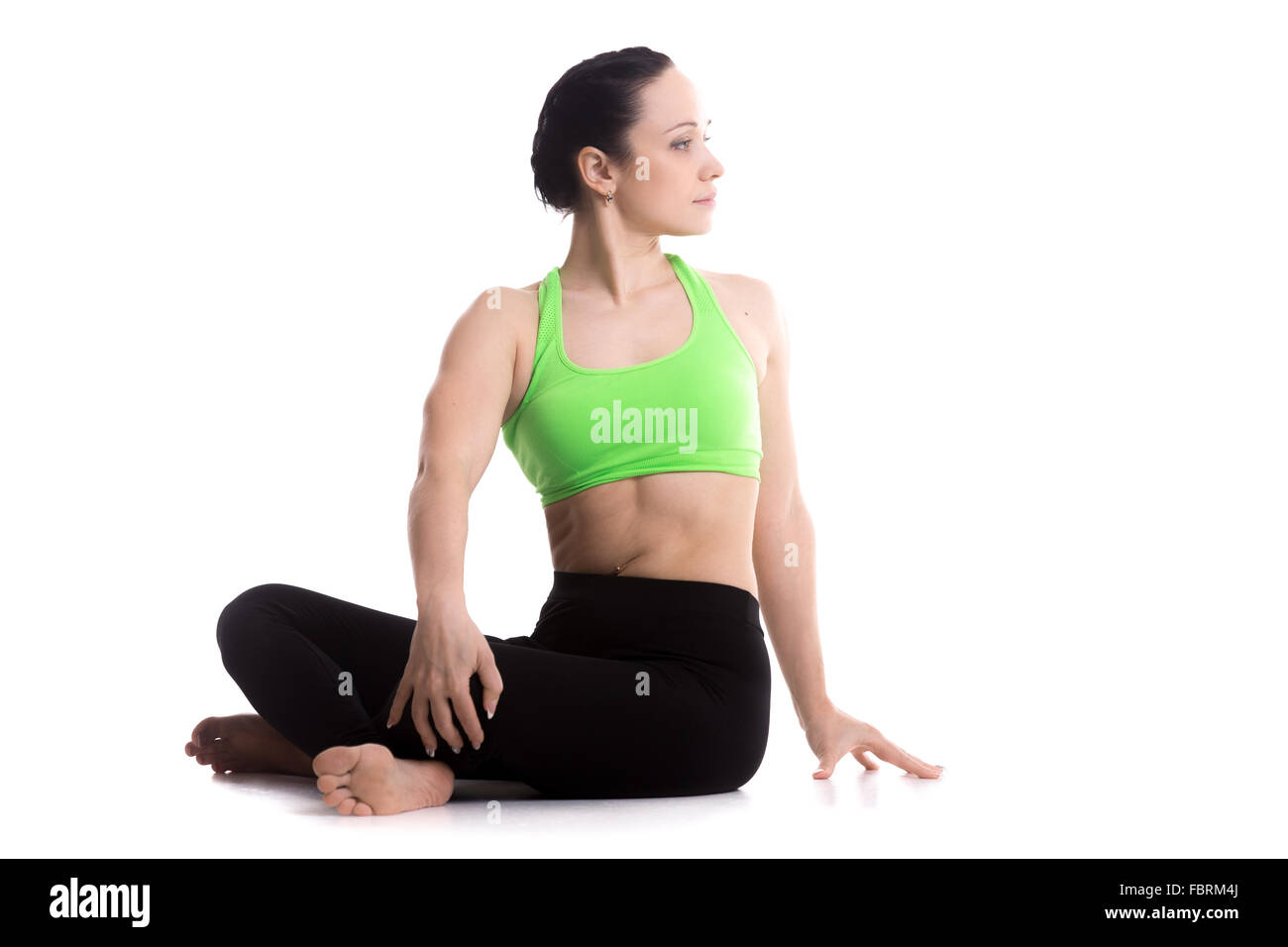Serene girl practicing yoga, Revolved easy pose, gentle spinal twist, parivrtta sukhasana, asana for flexible spine - Stock Image