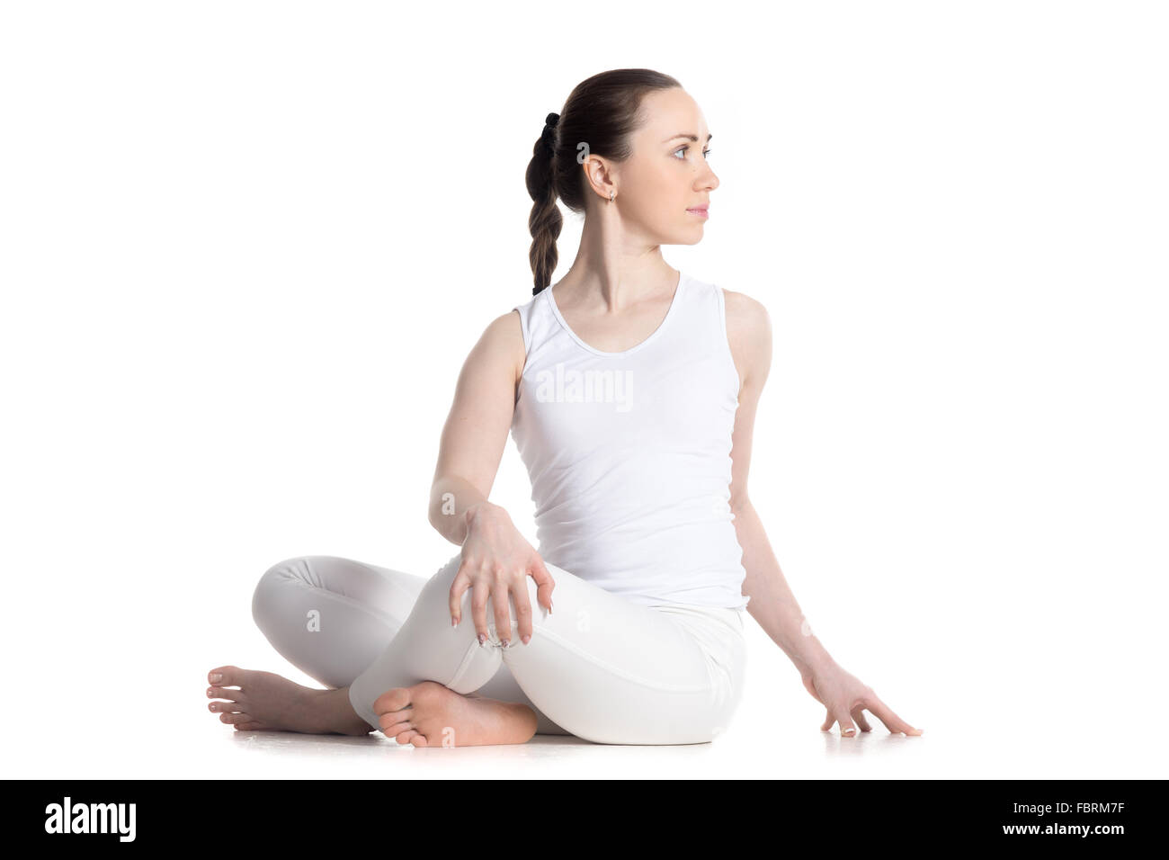 Sporty beautiful young woman in white sportswear practicing yoga, sitting cross legged in Revolved easy pose, spinal - Stock Image