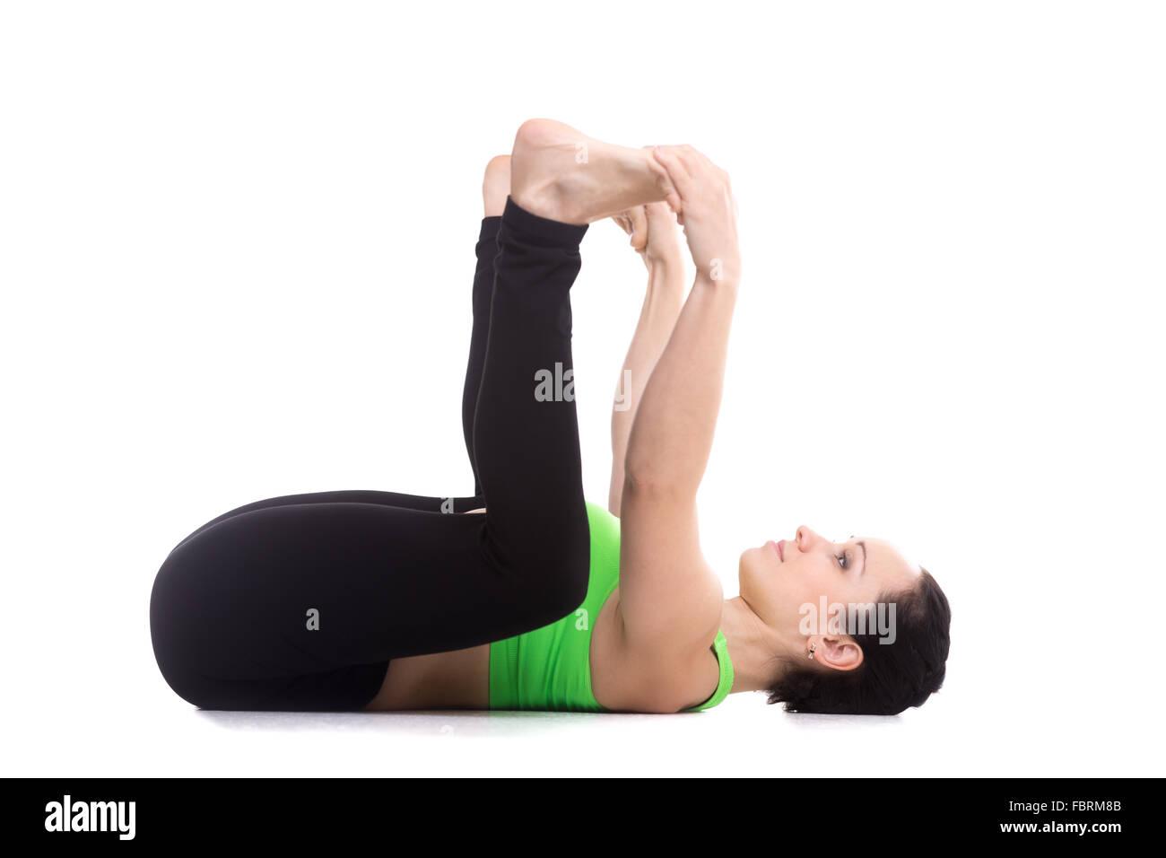 Sporty girl on white background lying in yoga Happy Baby pose, Ananda Balasana, relaxing, aligning back, stretching - Stock Image