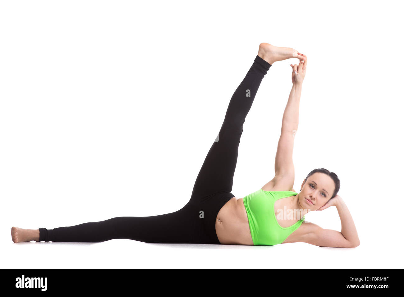 Beautiful slim girl doing fitness workout, exercise for toning belly, stretching legs, Anantasana, Side-Reclining - Stock Image