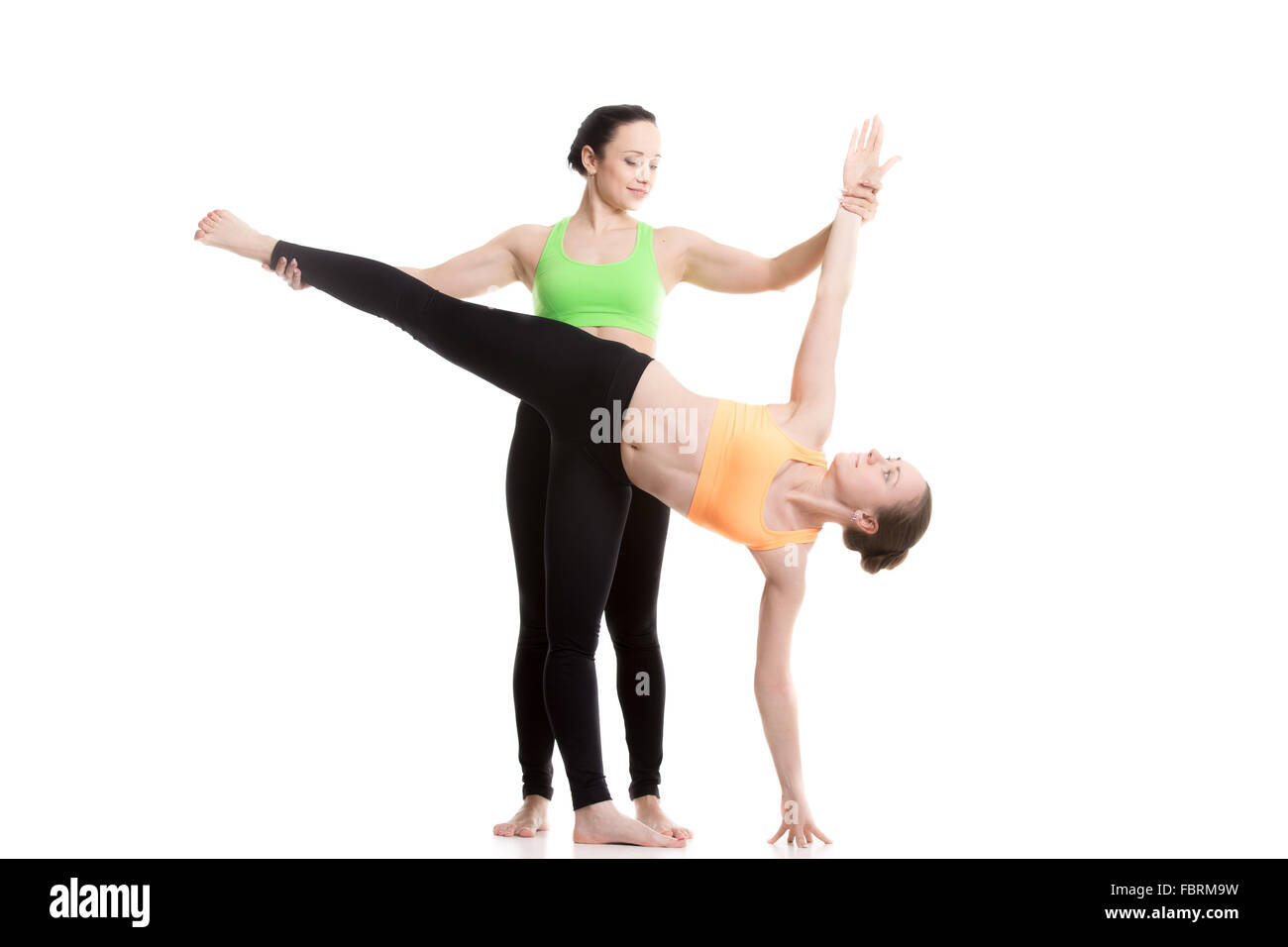 Two beautiful sporty girls practice yoga with partner, coach helps student, doing balance exercise Half Moon Pose, - Stock Image