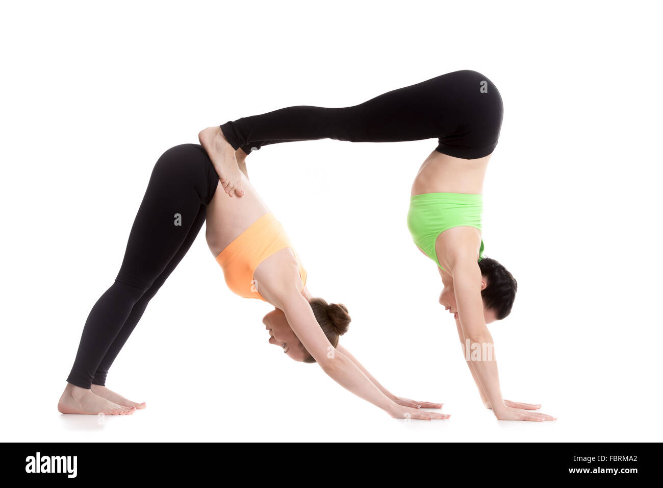 Two Sporty Girl On White Background Doing Acroyoga Yoga With Partner Downward Facing Dog Pose Adho Mukha Svanasana