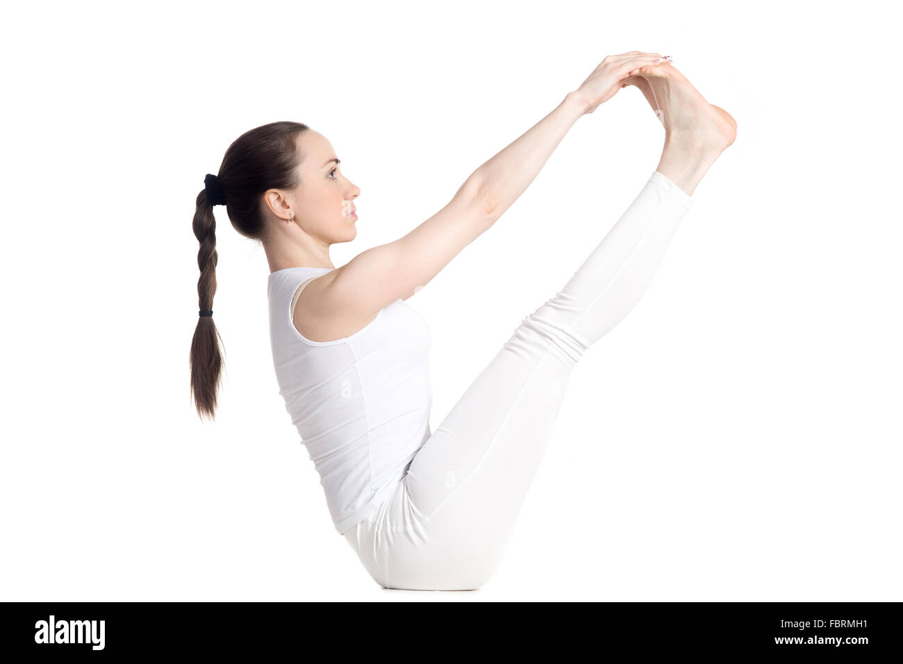 Sporty beautiful young woman in white sportswear doing exercises for legs and abs, sitting in Ubhaya Padangusthasana - Stock Image