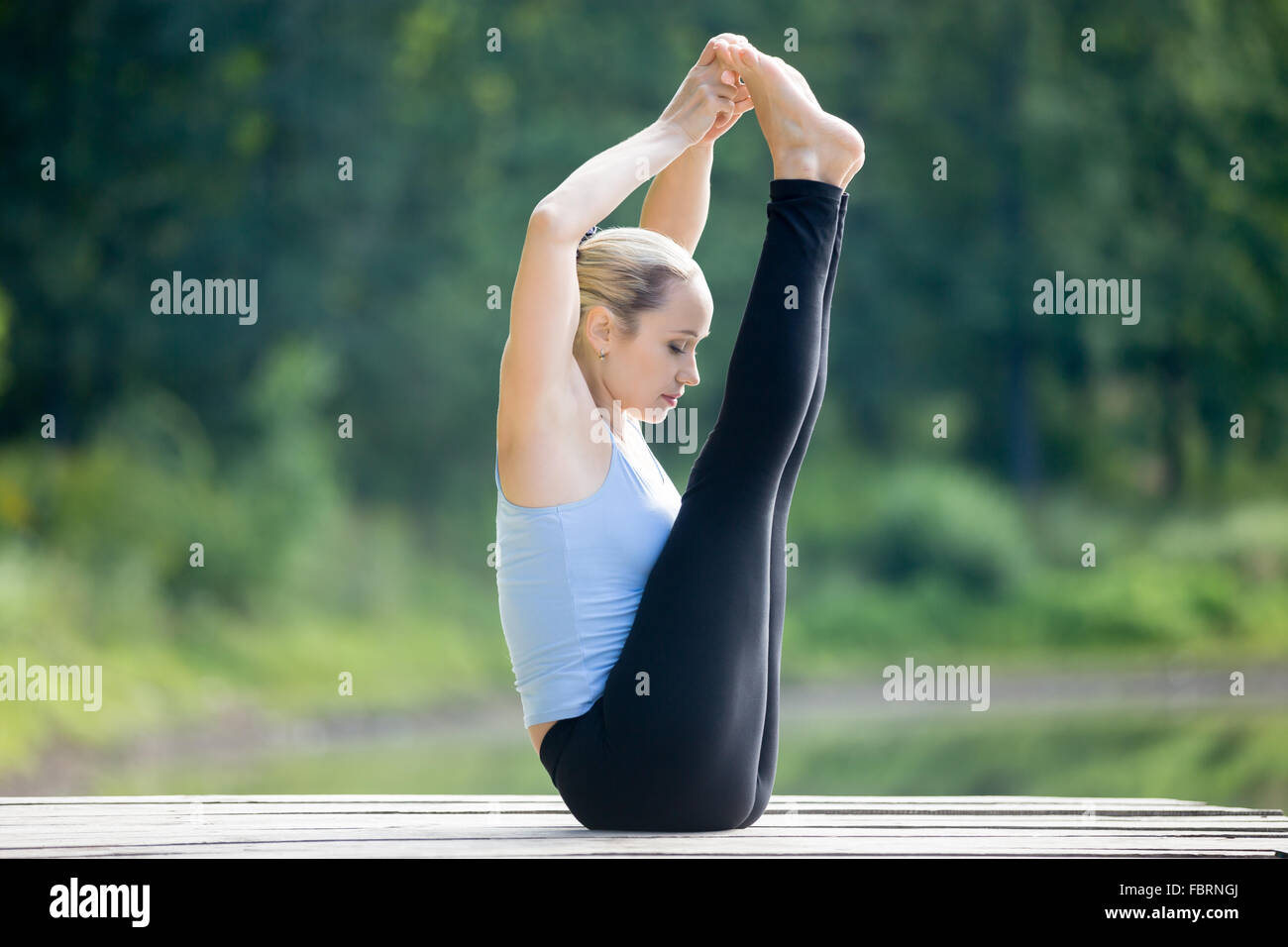 Serene fit young beautiful woman doing yoga training outdoors in park on summer day, sitting in Ubhaya Padangusthasana, - Stock Image