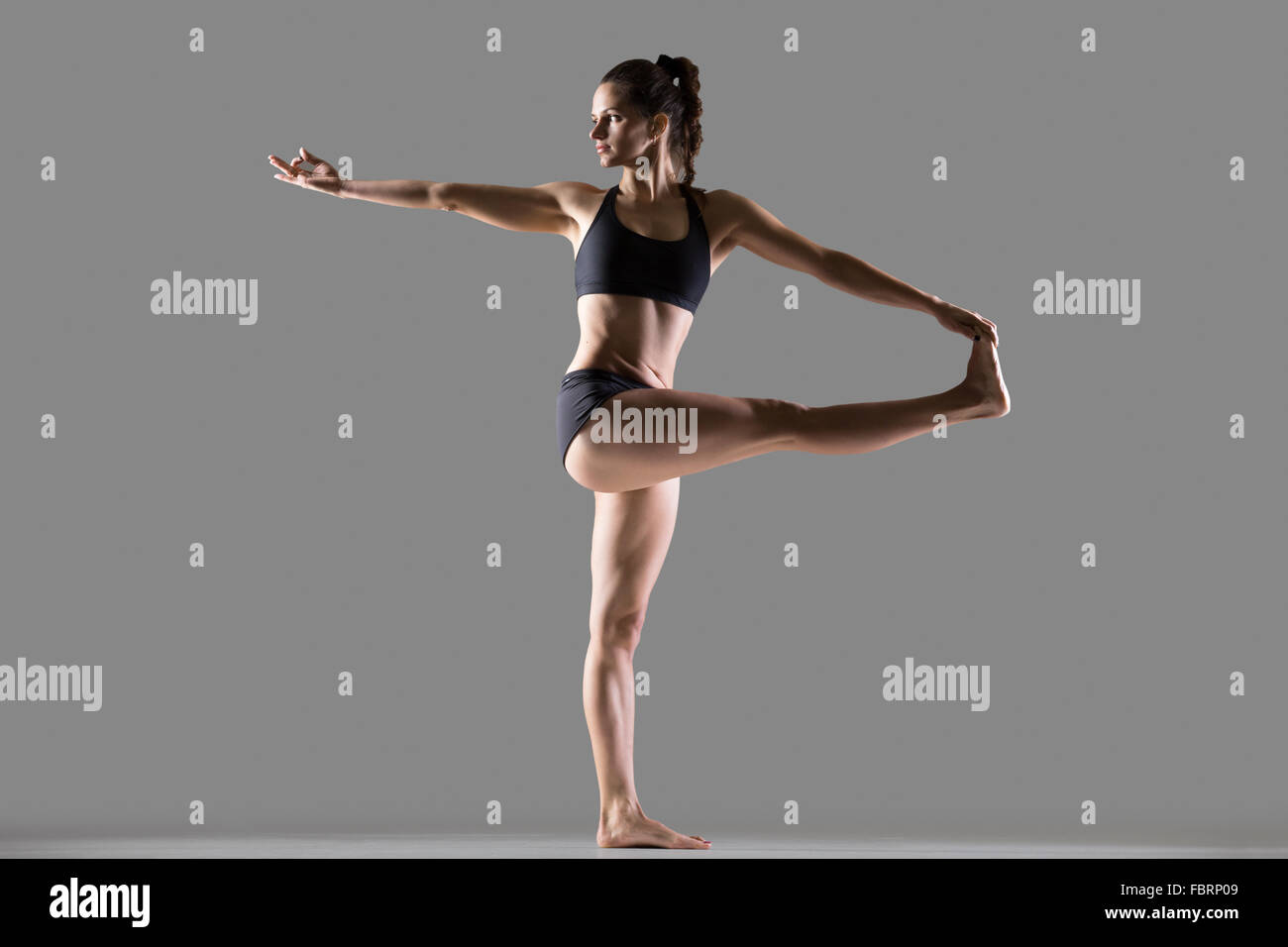 Portrait of beautiful young fit woman in sportswear doing sport exercise, Parivrtta Hasta Padangusthasana, Revolved - Stock Image