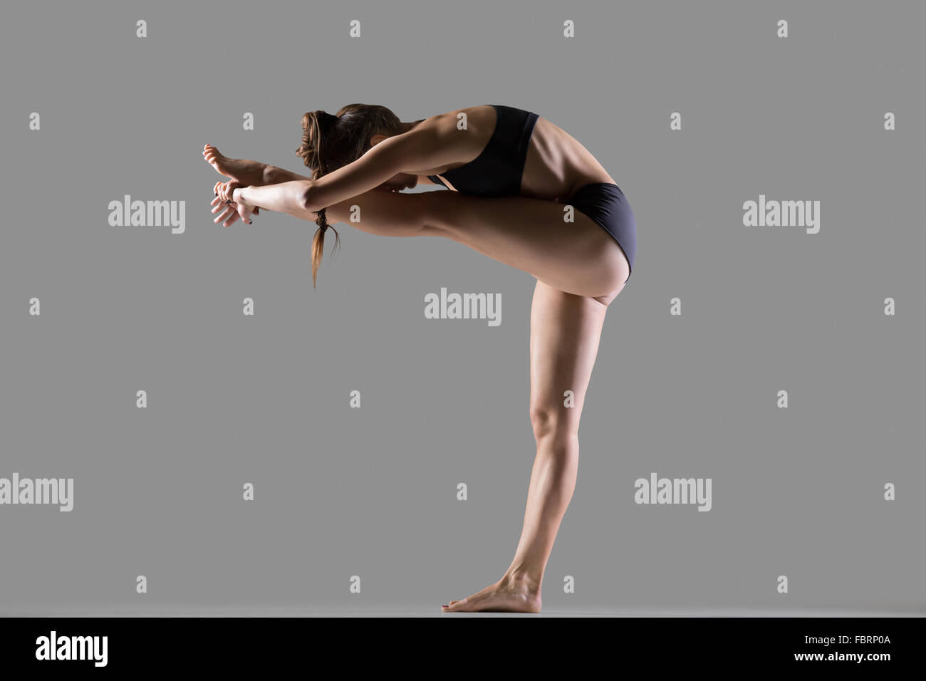 Beautiful young fit woman in sportswear doing sport exercise, bending in variation of Utthita Hasta Padangusthasana, - Stock Image