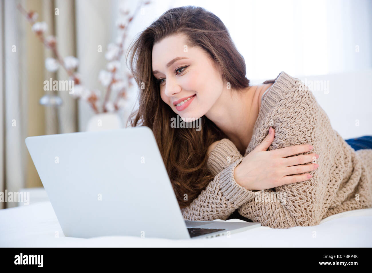 Smiling pretty young woman in beige knitted sweater lying on bed with laptop in the room Stock Photo