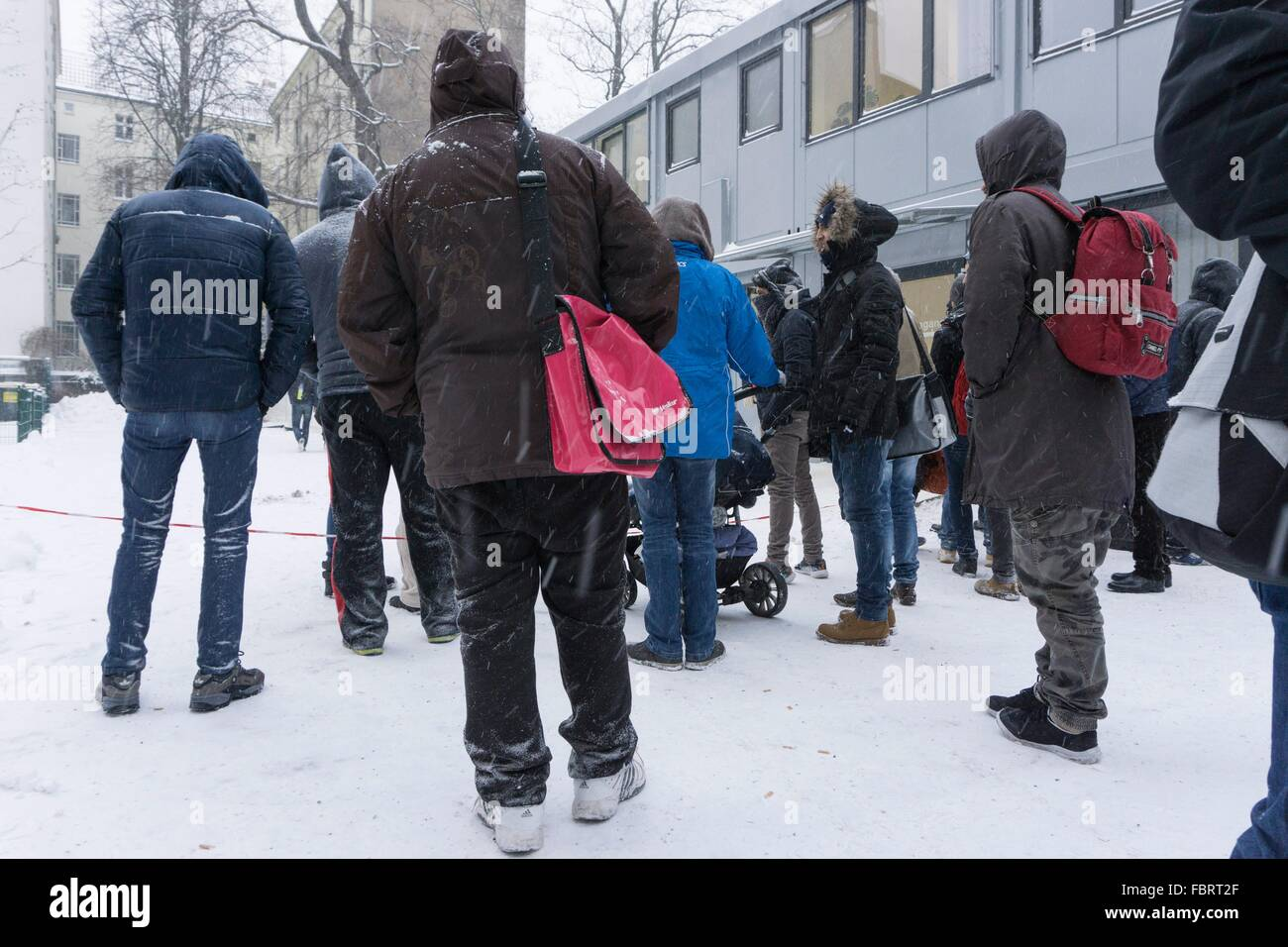 Refugees wait during heavy snowfall outside the Central Registration Office for Asylum Seekers of the State Office Stock Photo