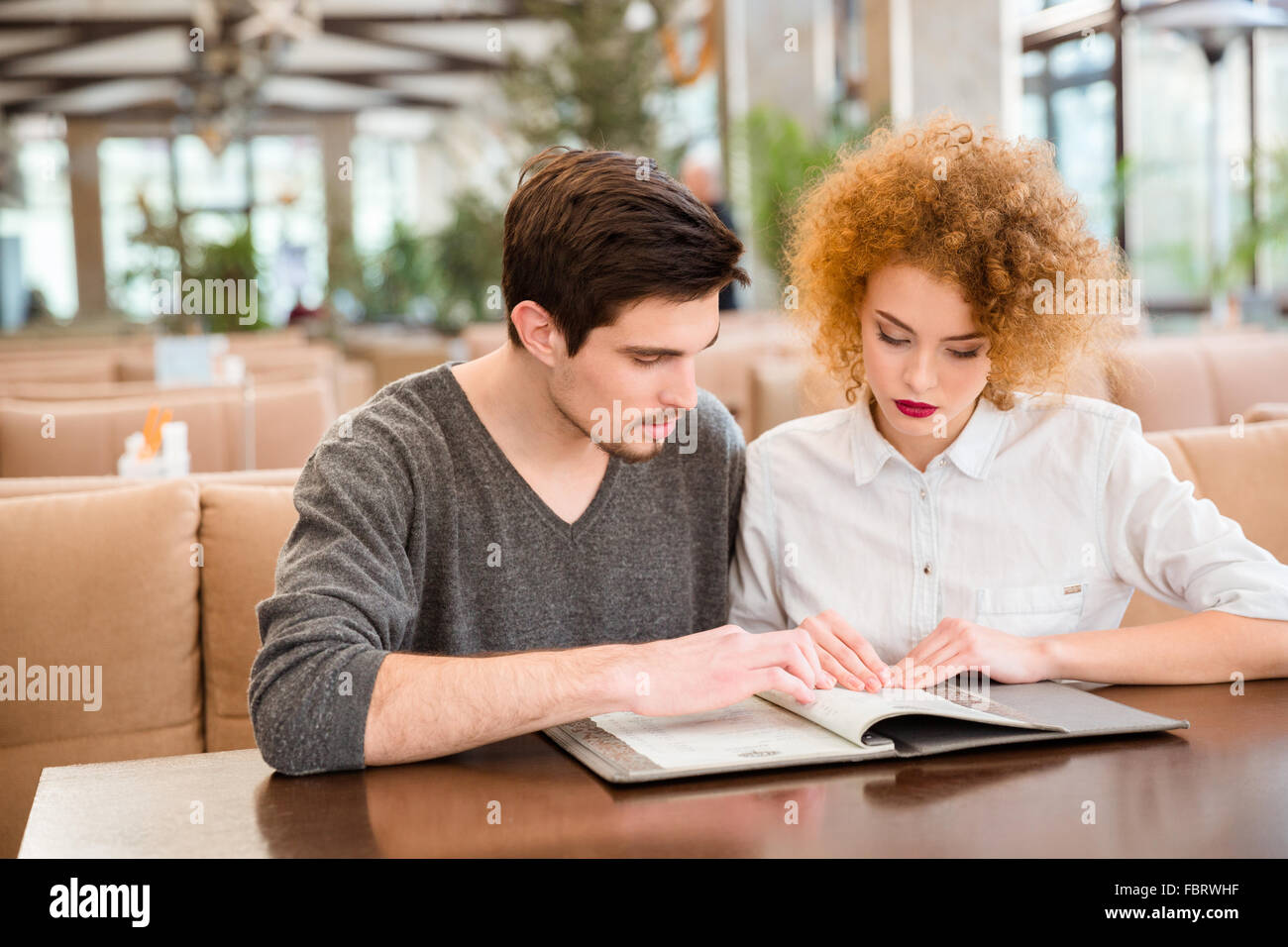 Portrait of a young couple reading menu in restaurant - Stock Image
