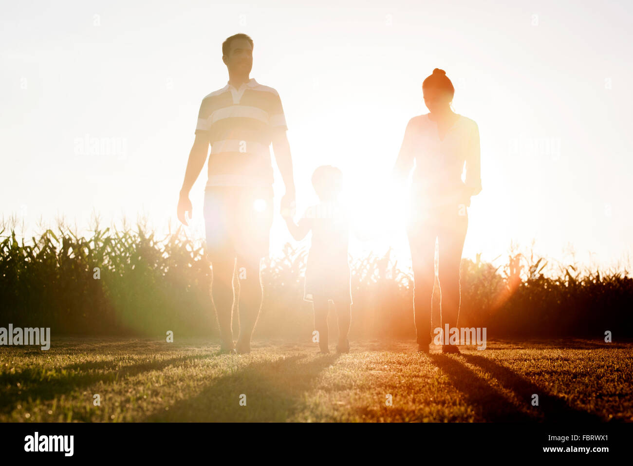 Family with little boy walking together outdoors - Stock Image