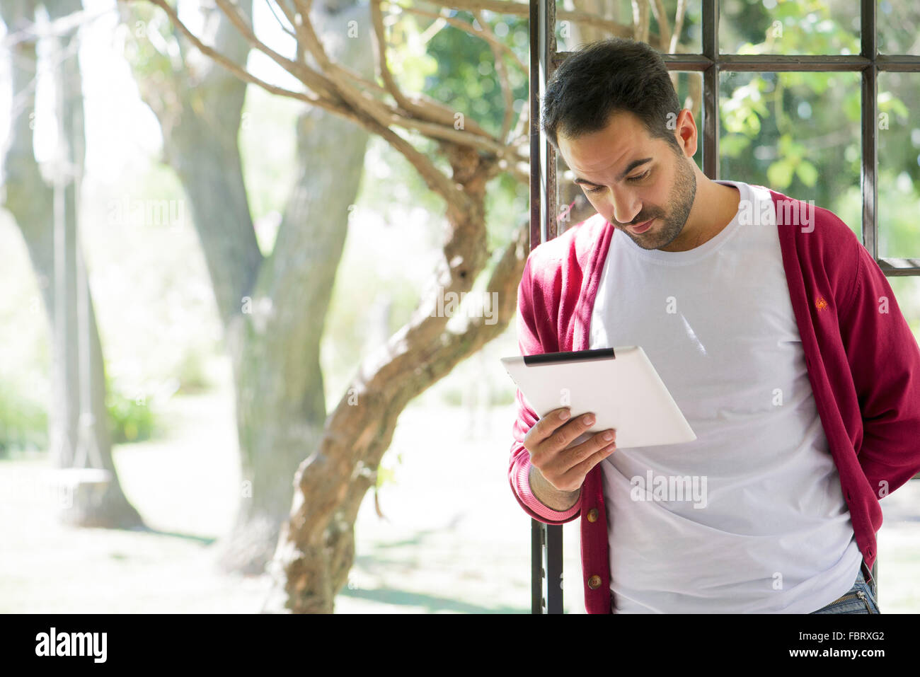 Man using digital tablet at home - Stock Image
