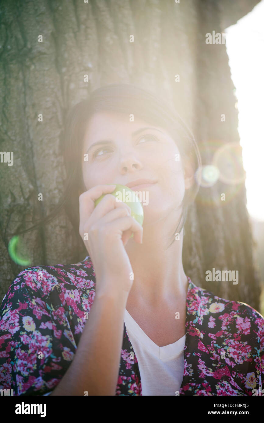 Woman holding apple, looking up dreamily, portrait - Stock Image