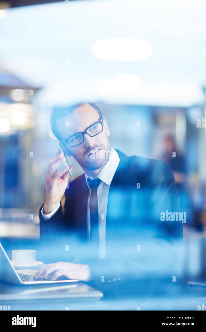 Confident businessman speaking on the phone and networking in cafe - Stock Image