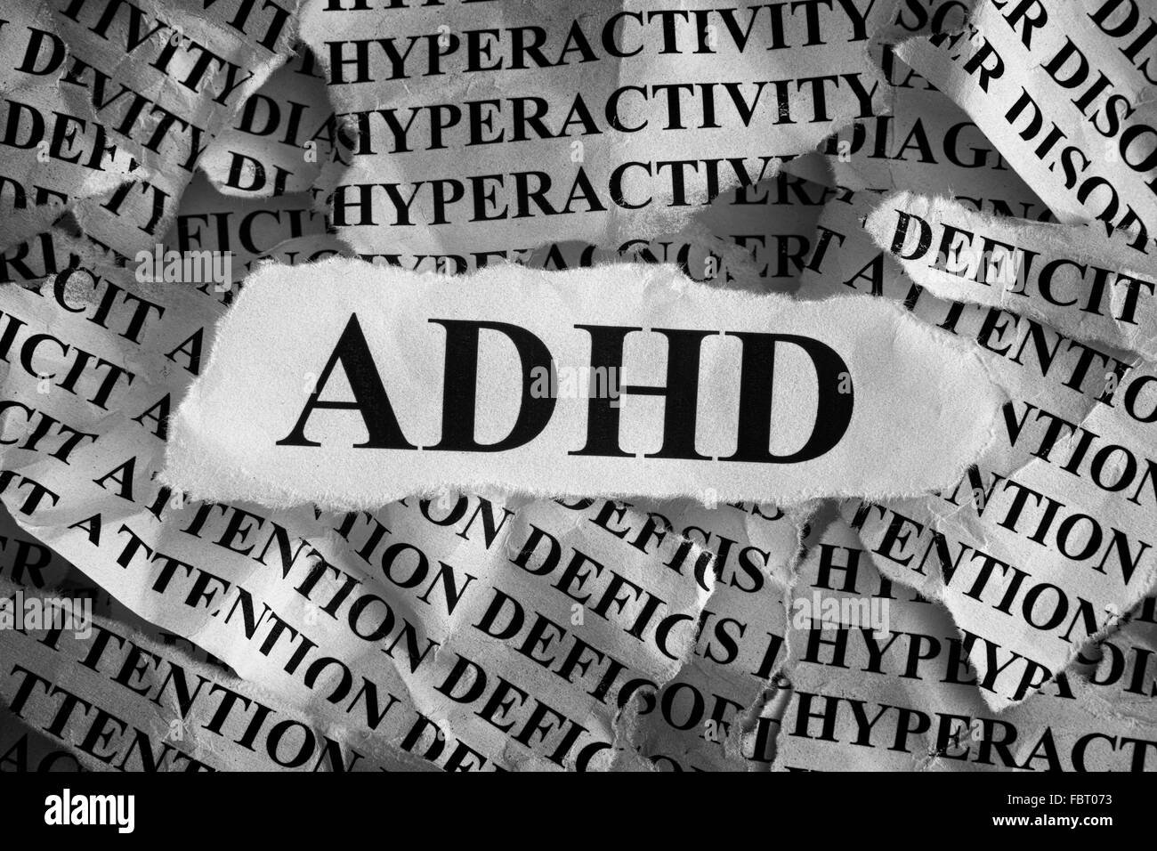 Torn pieces of paper with abbreviation ADHD. Concept Image. Black and White. ADHD is Attention deficit hyperactivity - Stock Image