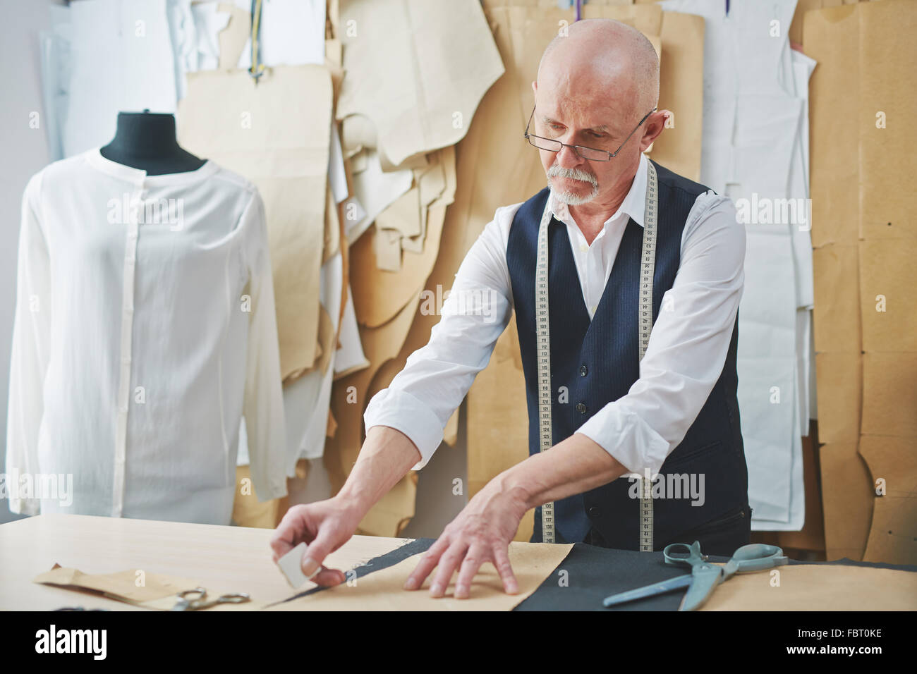 Mature tailor cutting out pattern in tailoring shop - Stock Image