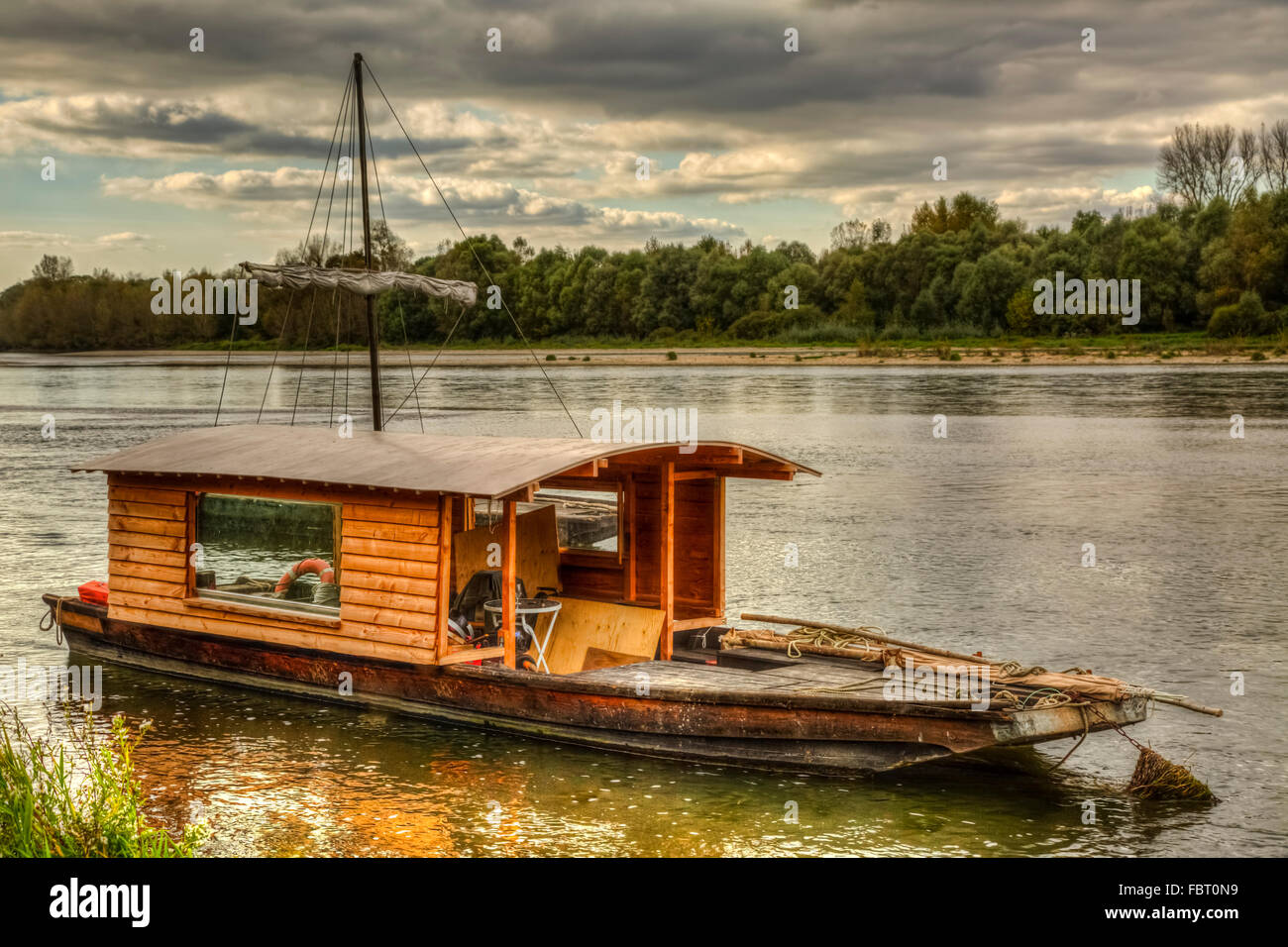 Wooden boat on the Loire Valley in France during an autumn evening day. Stock Photo