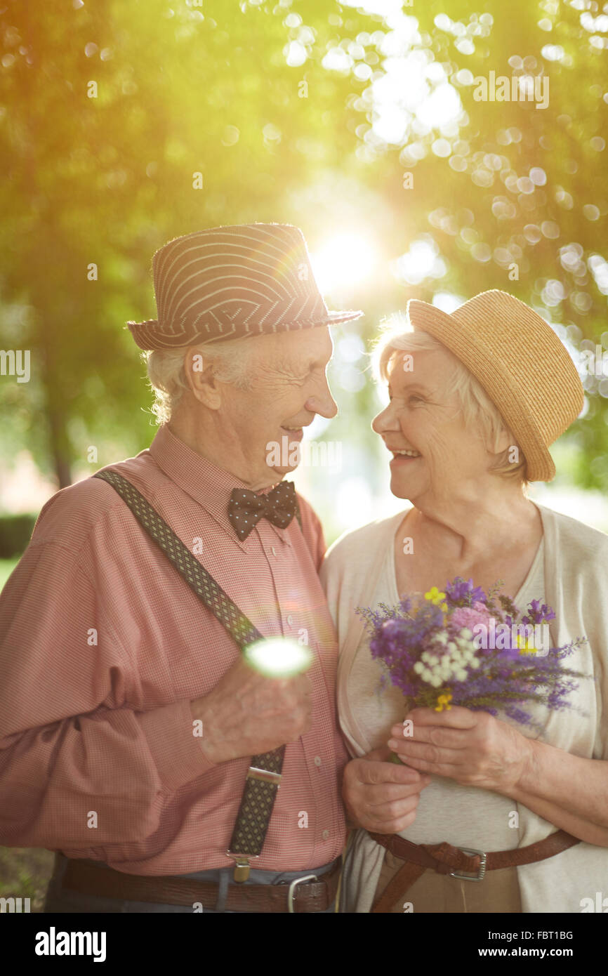 Amorous seniors looking at one another with smiles in natural environment - Stock Image
