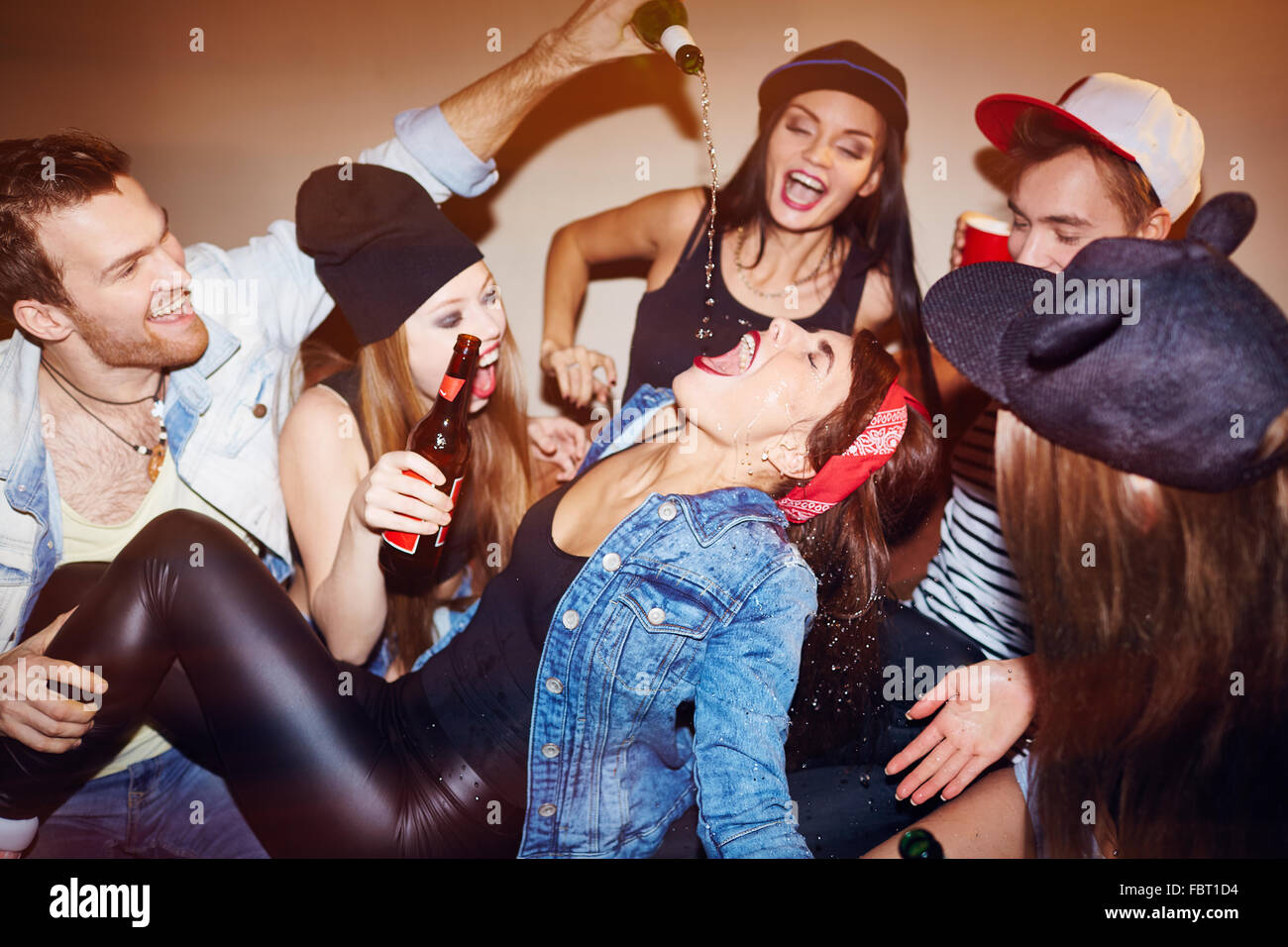 Ecstatic friends pouring beer into girl mouth at swag party - Stock Image