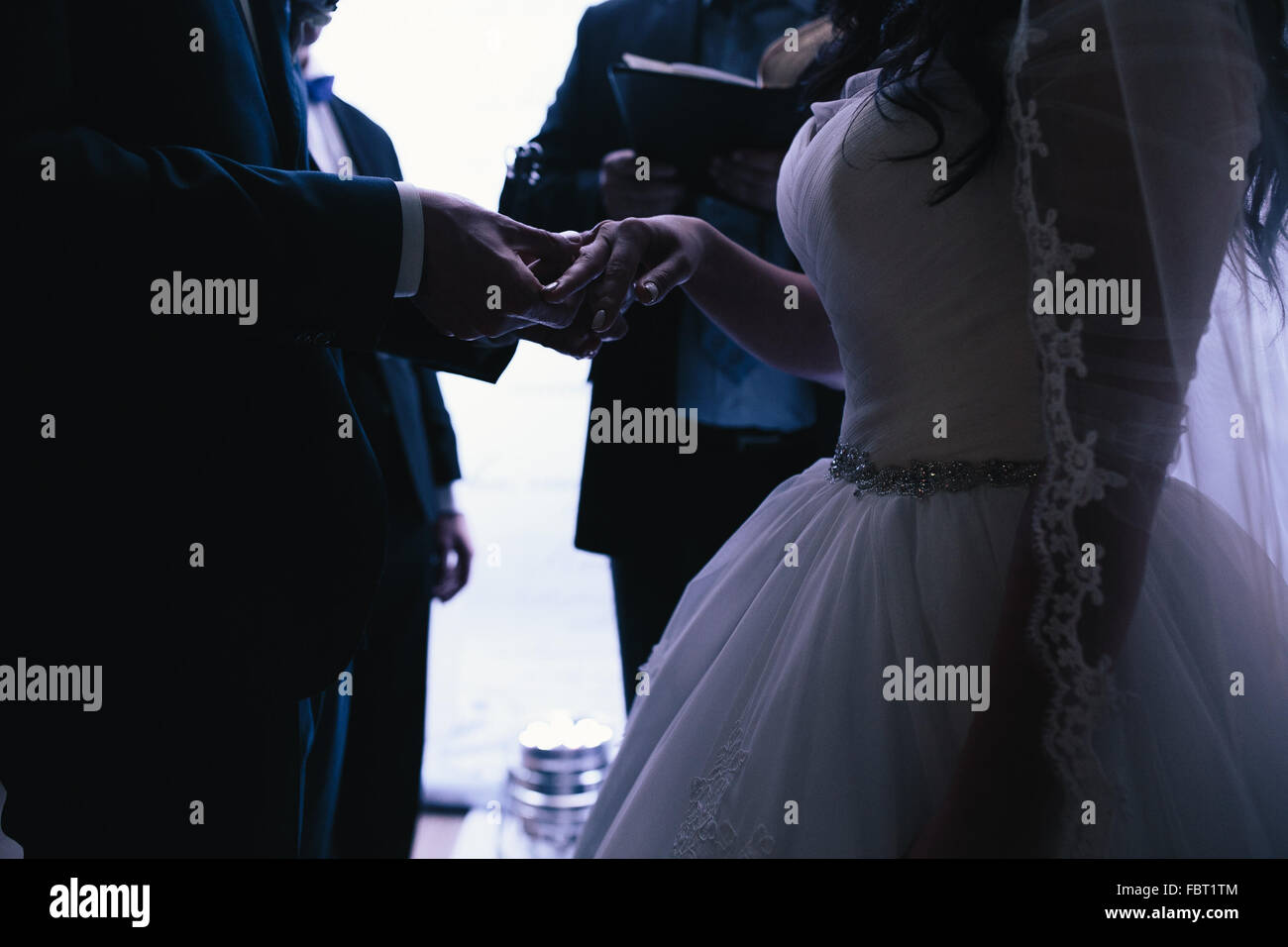 groom wears the ring bride - Stock Image