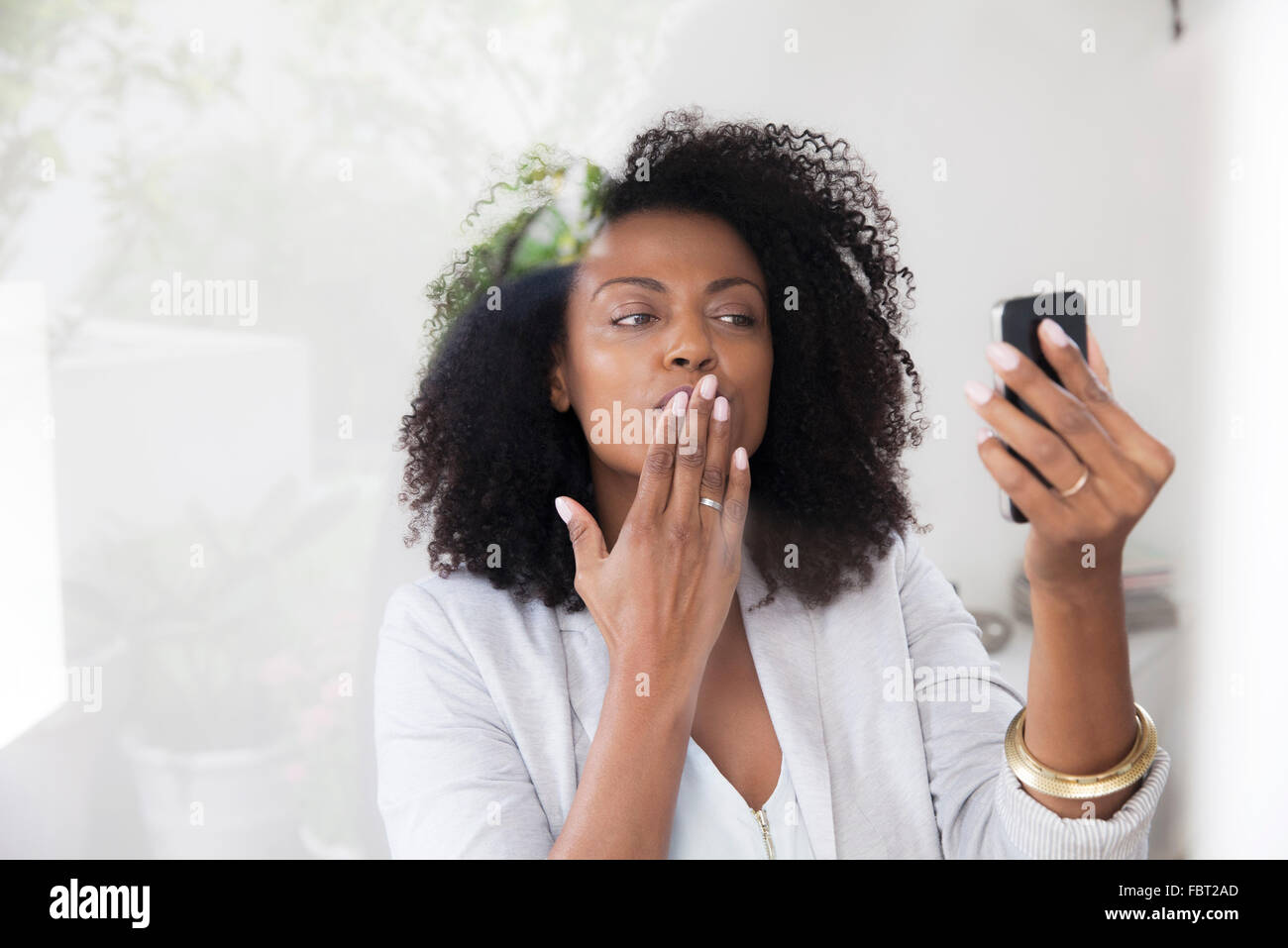 Woman blowing kiss at smartphone while doing video chat - Stock Image