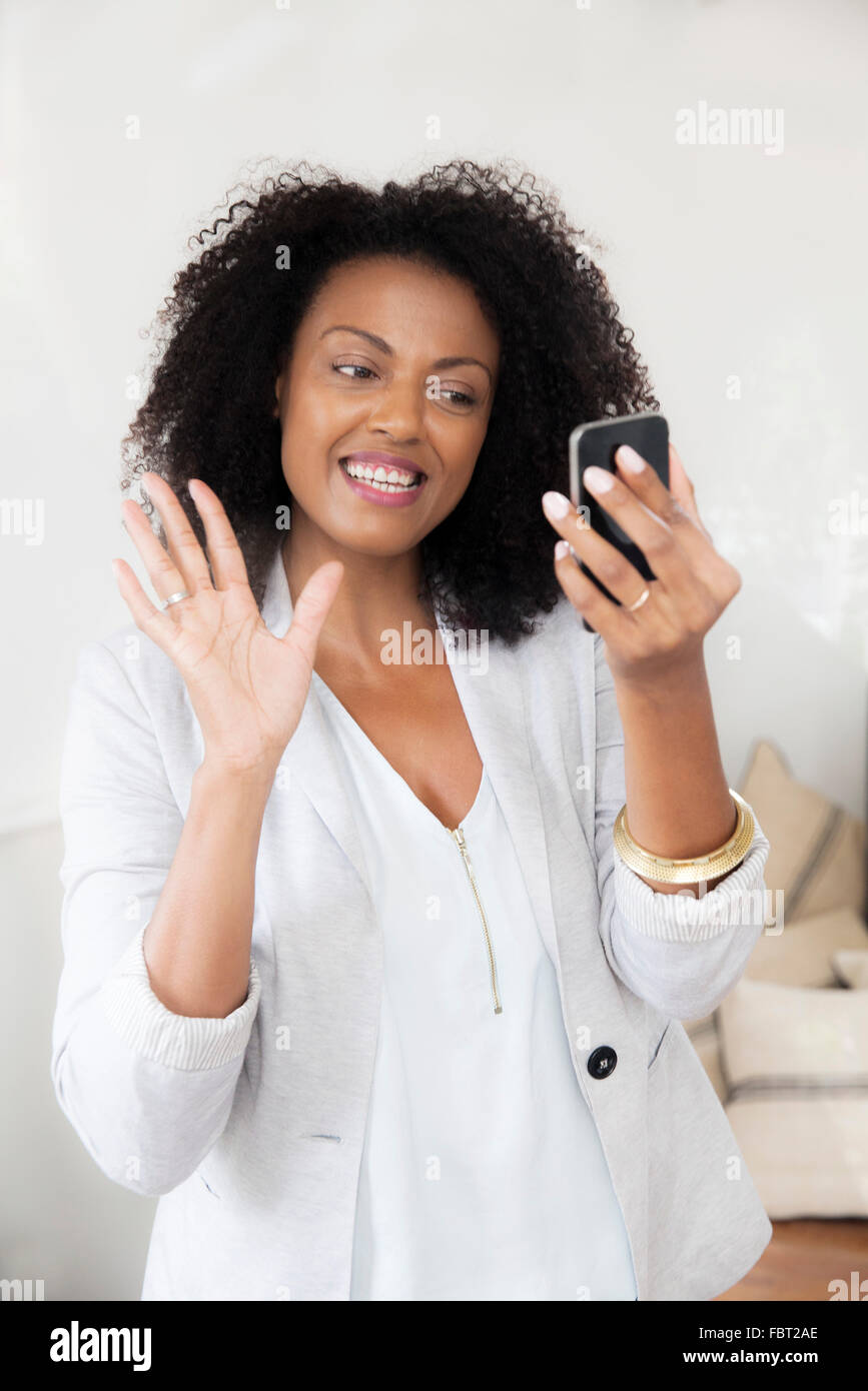 Woman waving at smartphone while doing video chat - Stock Image