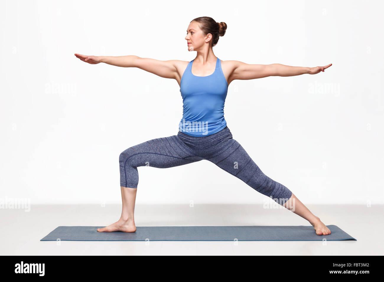 Woman practices yoga asana utthita Virabhadras - Stock Image