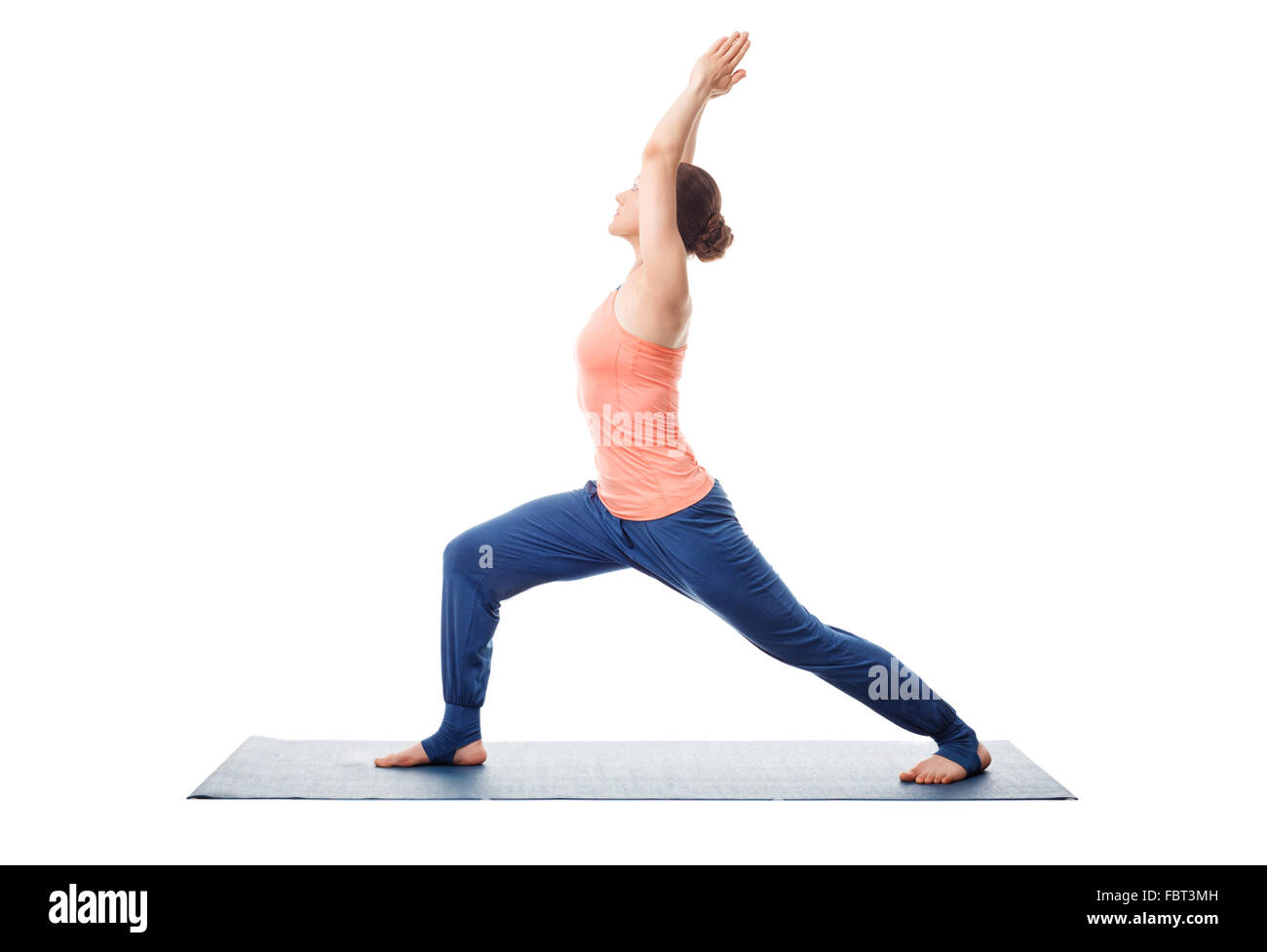 Woman practices yoga Warrior asana - Stock Image