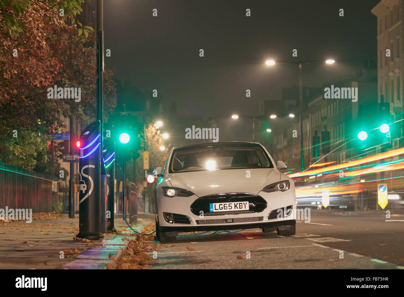 Tesla luxury electric car at a charging point in Kensington, London - Stock Image