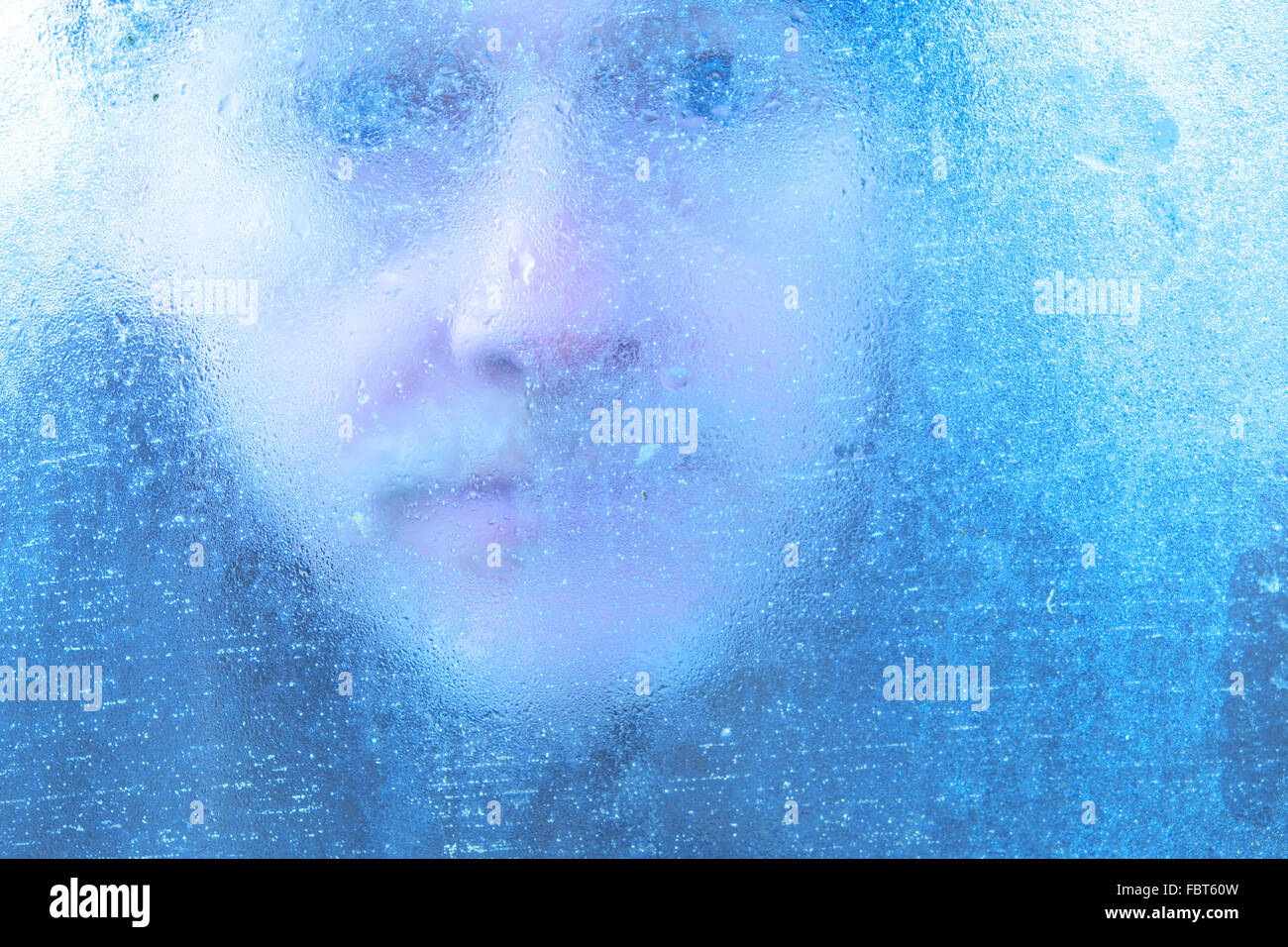 Winter man looking through window covered in ice and condensation UK - Stock Image