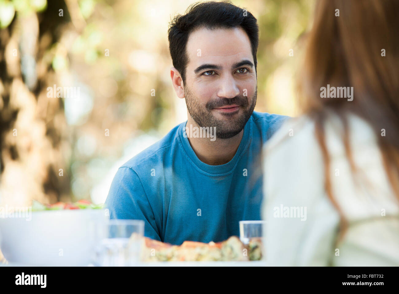Man having meal outdoors with date Stock Photo