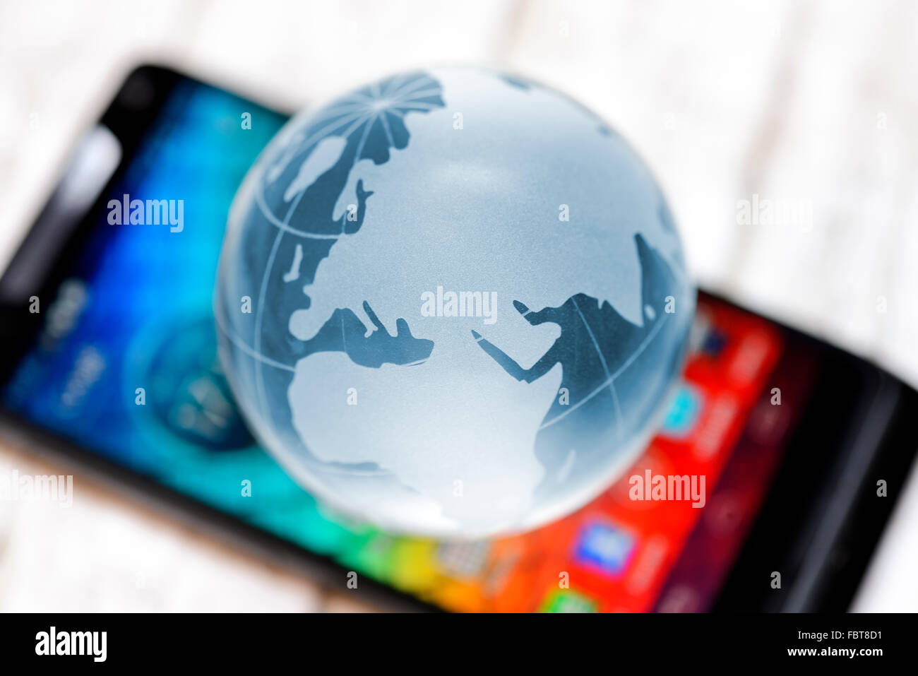 Glass globe on smartphone, roaming charges - Stock Image