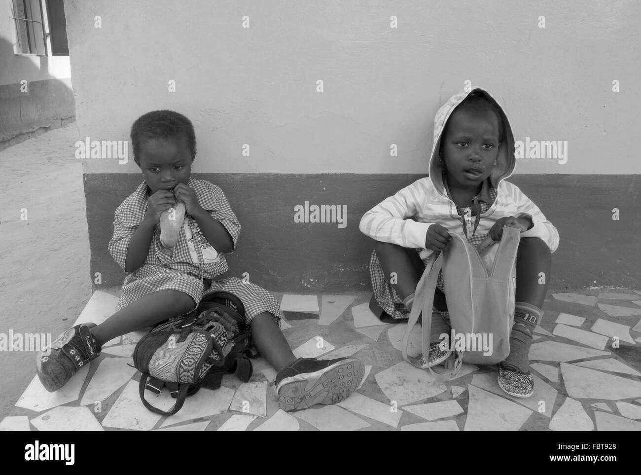 Lunch break for two black infant girls at a charity run school in the back streets of Kololi Gambia - Stock Image