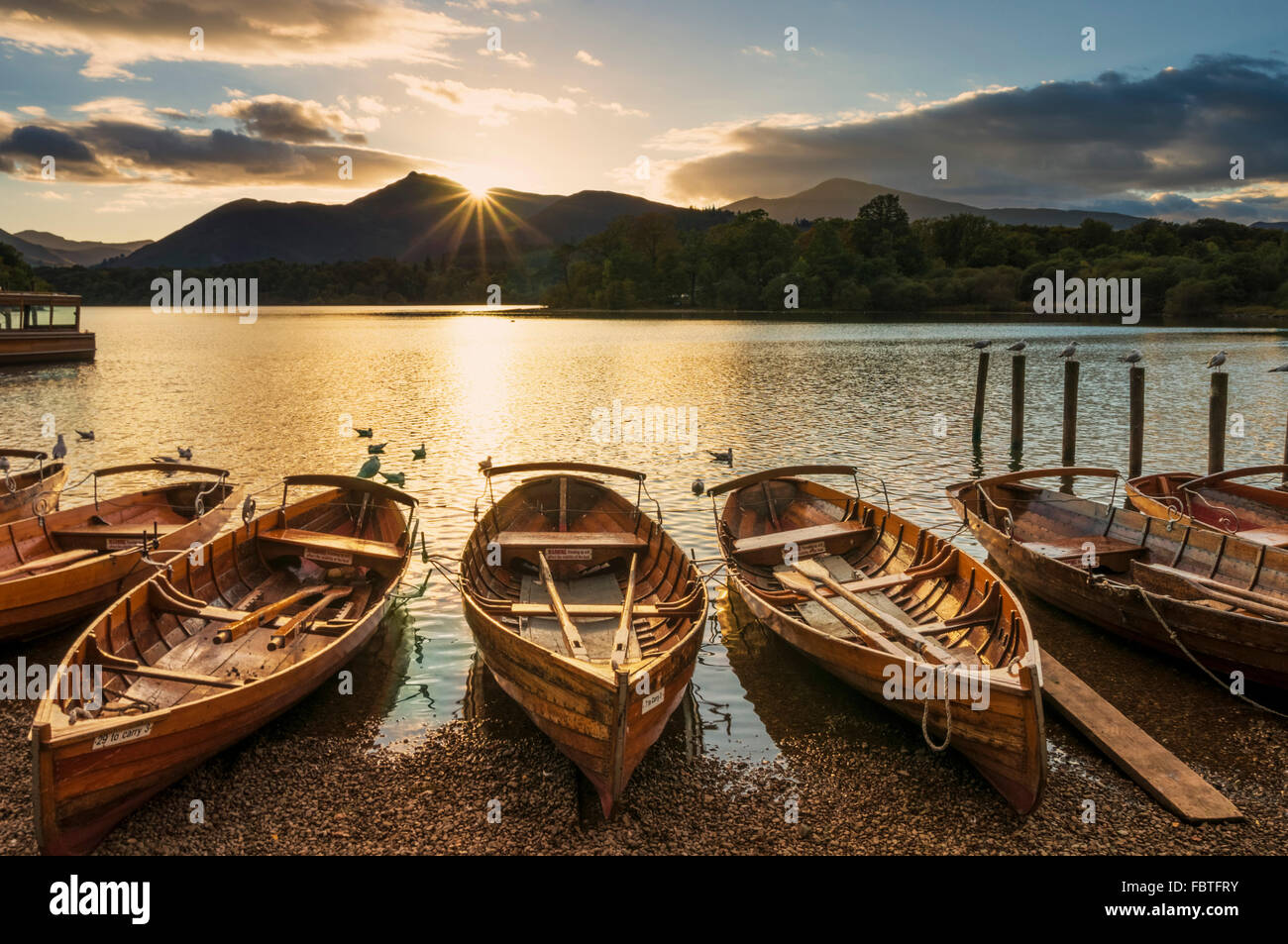 Wooden rowing boats with sunset sky Keswick Landing Stages Derwent Water Keswick Lake District Cumbria England UK - Stock Image