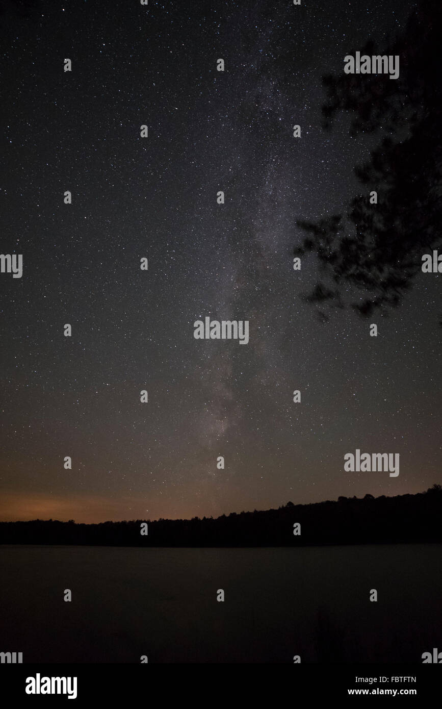 The stars Milky Way galaxy cuts through the sky, while an orange-yellow glow on the horizon shows light pollution. - Stock Image