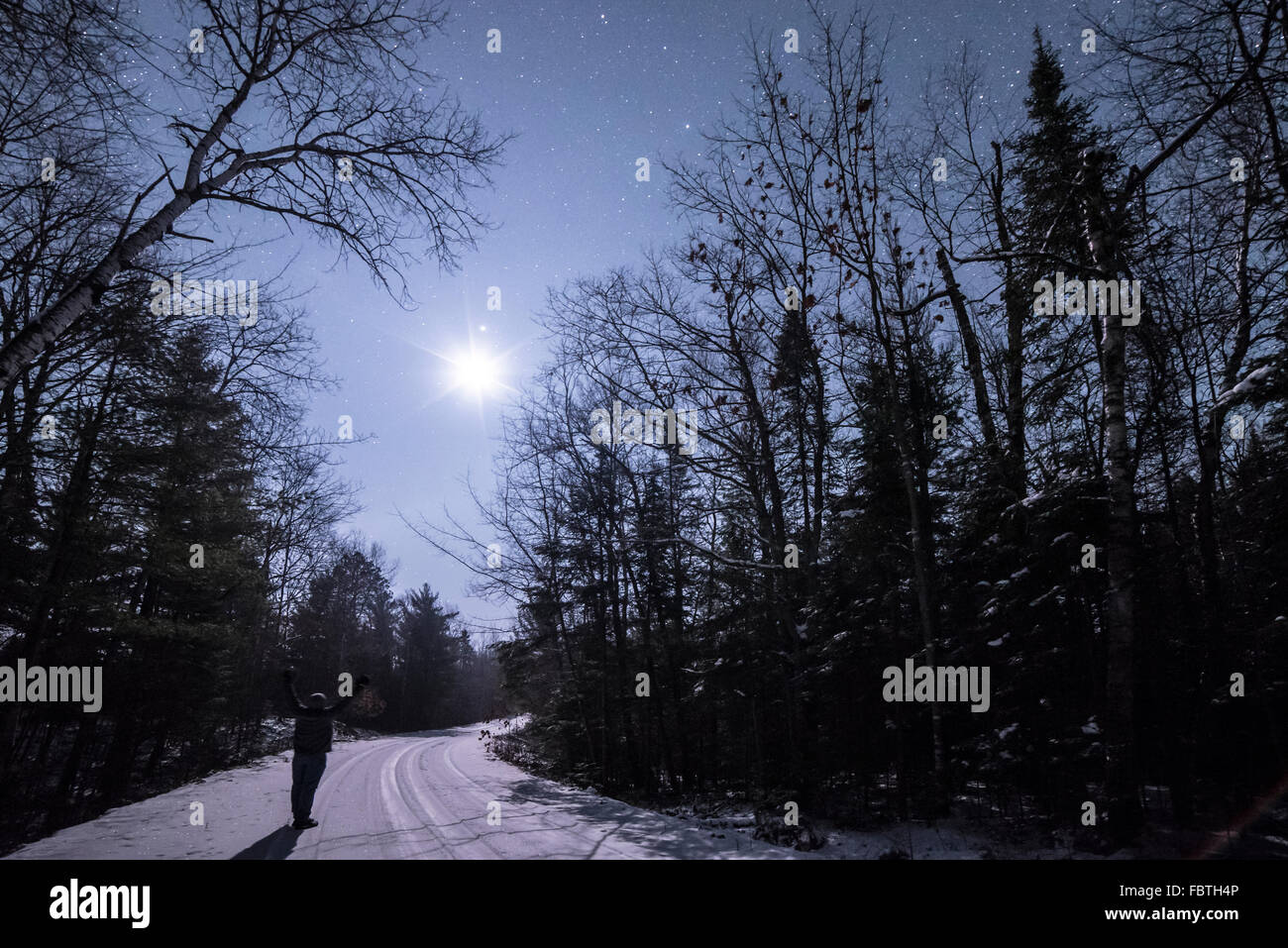 Standing on a snowy, forest road, arms raised in praise of the moon and the night sky. - Stock Image