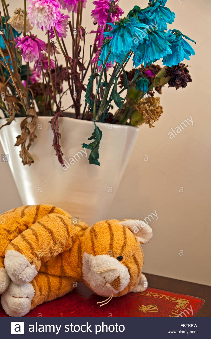 A forlorn looking soft toy next to a vase of wilting flowers Stock Photo