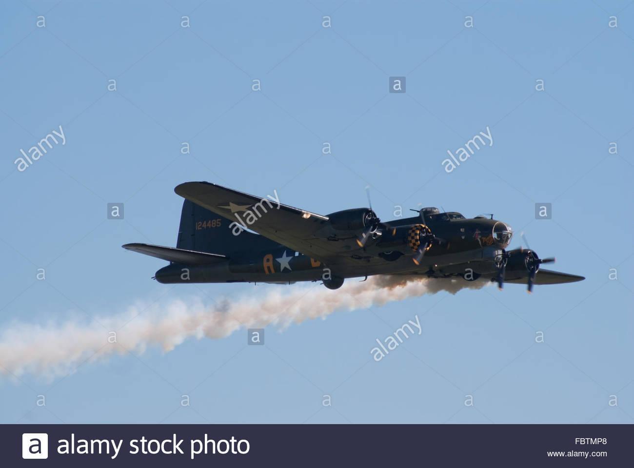 Boeing B-17 flies with smoke trail - Stock Image