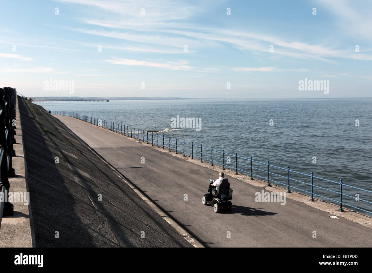 Hartlepool. A man driving a mobility scooter by the sea. - Stock Image