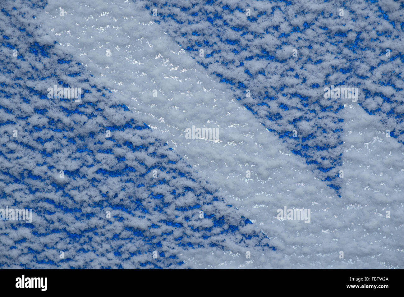 Snow on a reflective blue sign with a white directional arrow - Stock Image