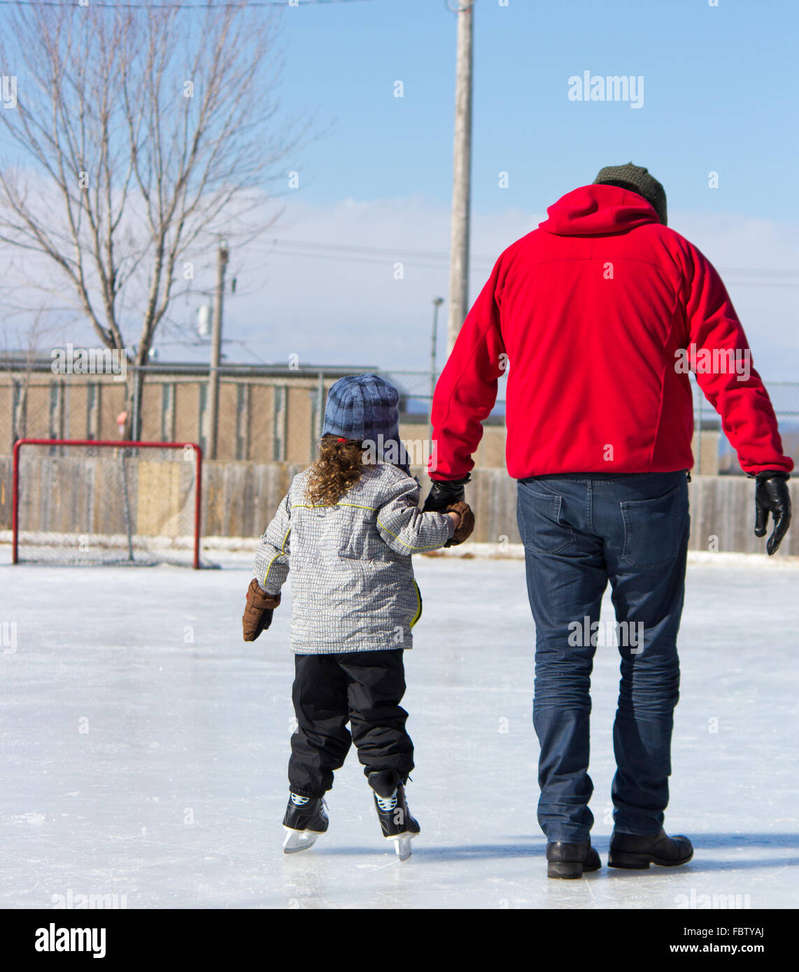 Father teaching daughter how to ice skate - Stock Image