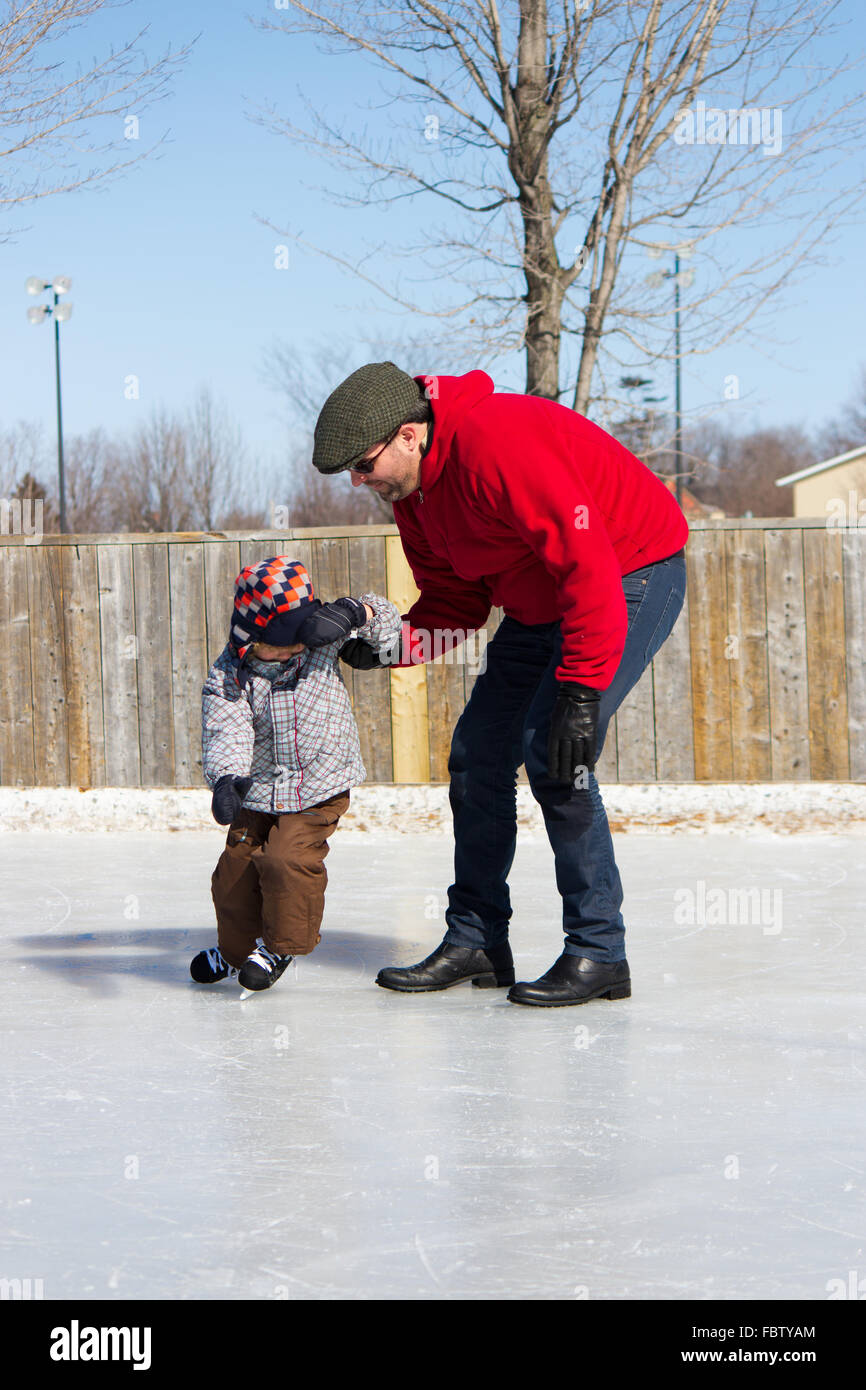 Father teaching son how to ice skate - Stock Image