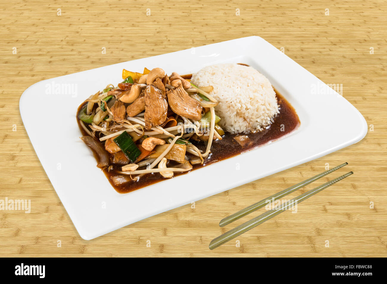 Chinese Asia Food. Pork, bean sprouts with vegetables, cashjew cores  and rice. Plate standing on a wood table with - Stock Image