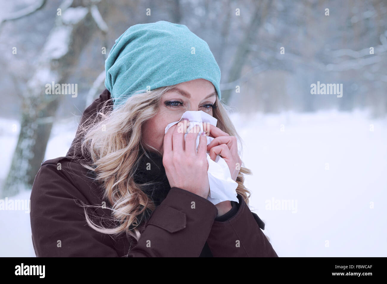 woman blowing her nose in winter - Stock Image