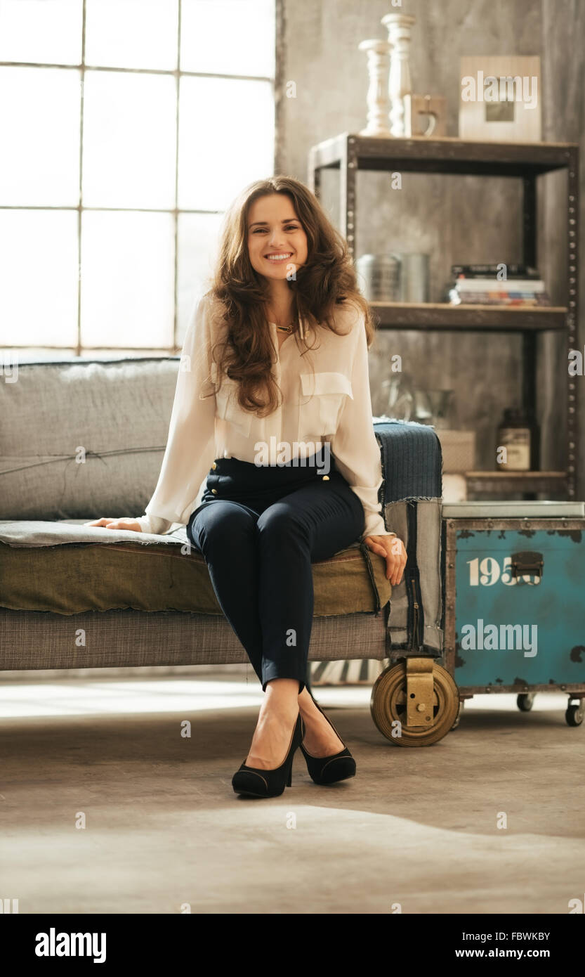 Smiling Brunet Woman In Elegant Clothing Sitting On Coach With Crossed Feet  In Loft Apartment