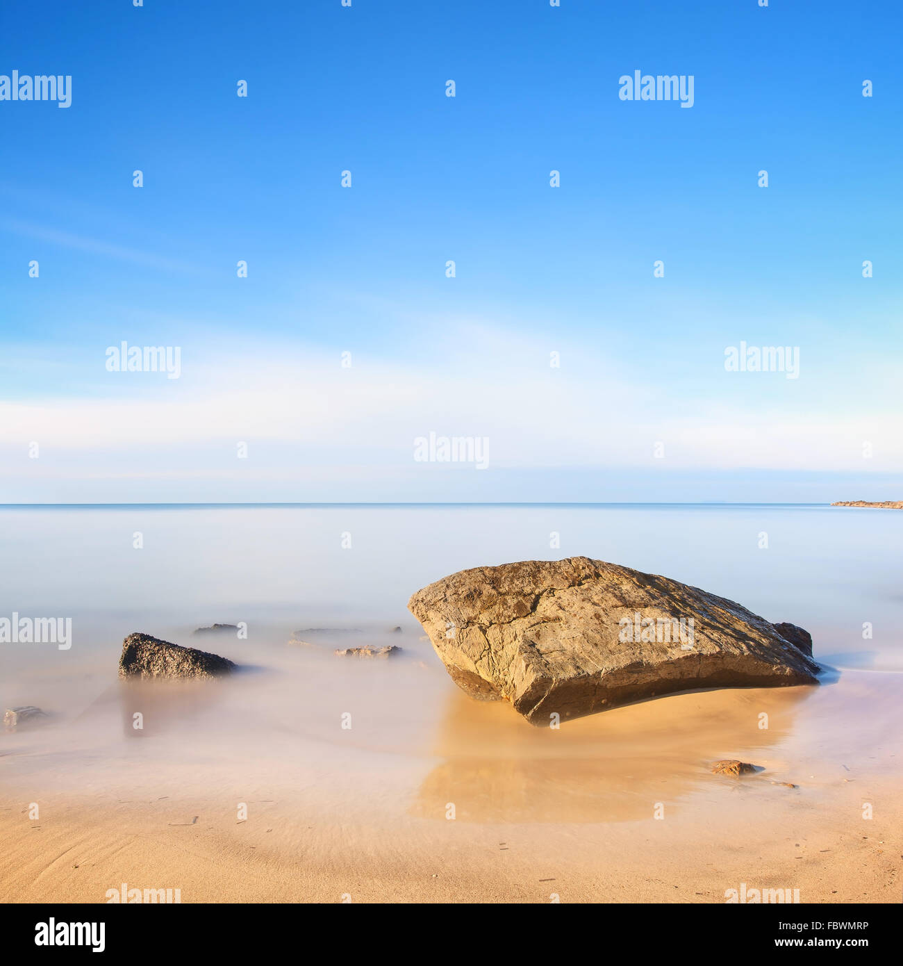 A flat rock on a golden sand beach and blue ocean. Long exposure photography. - Stock Image