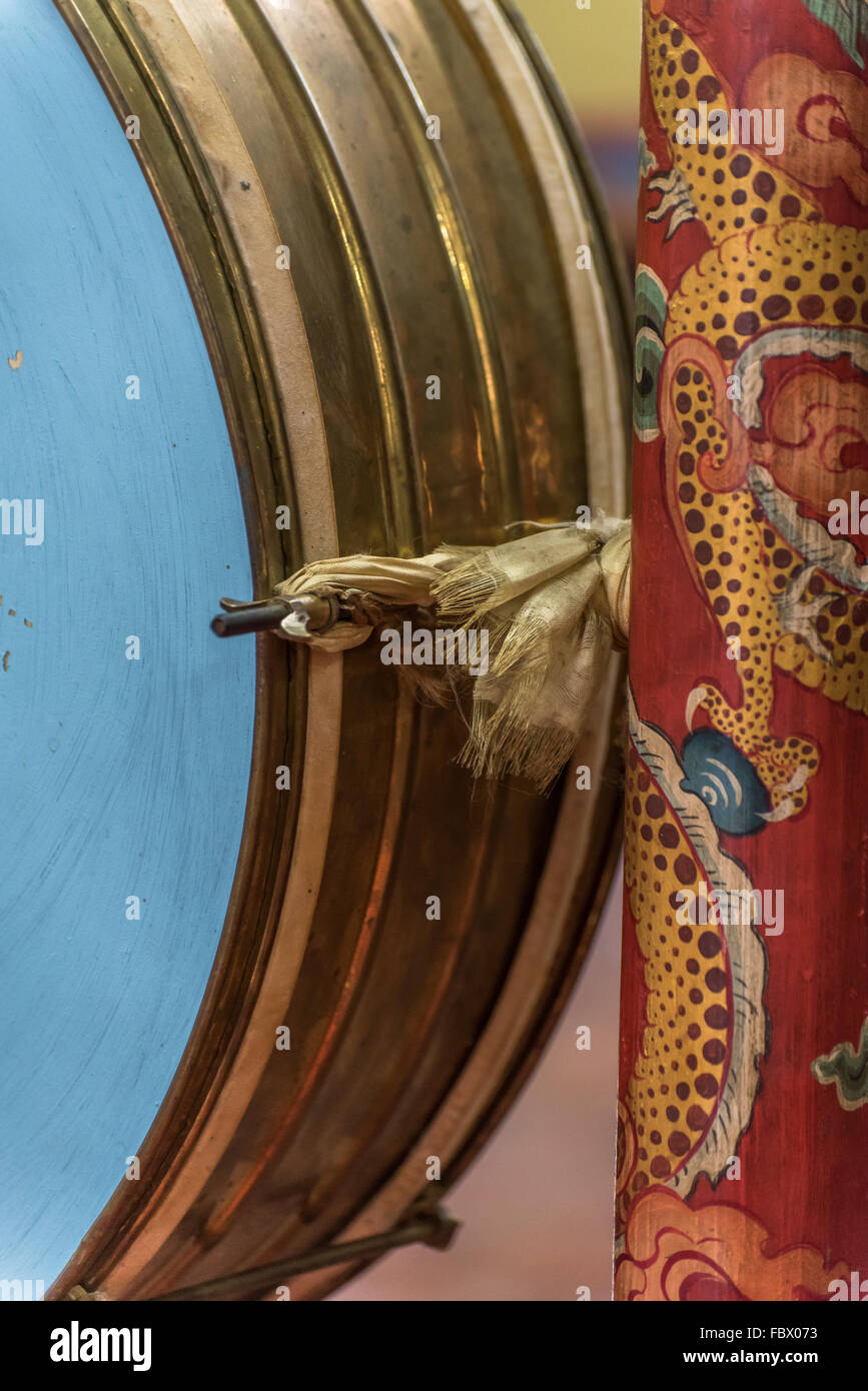 Brass rim and hand painted frame detail of an upright hanging drum. Buddhist artifacts and symbolism in Dirang Monastery. - Stock Image